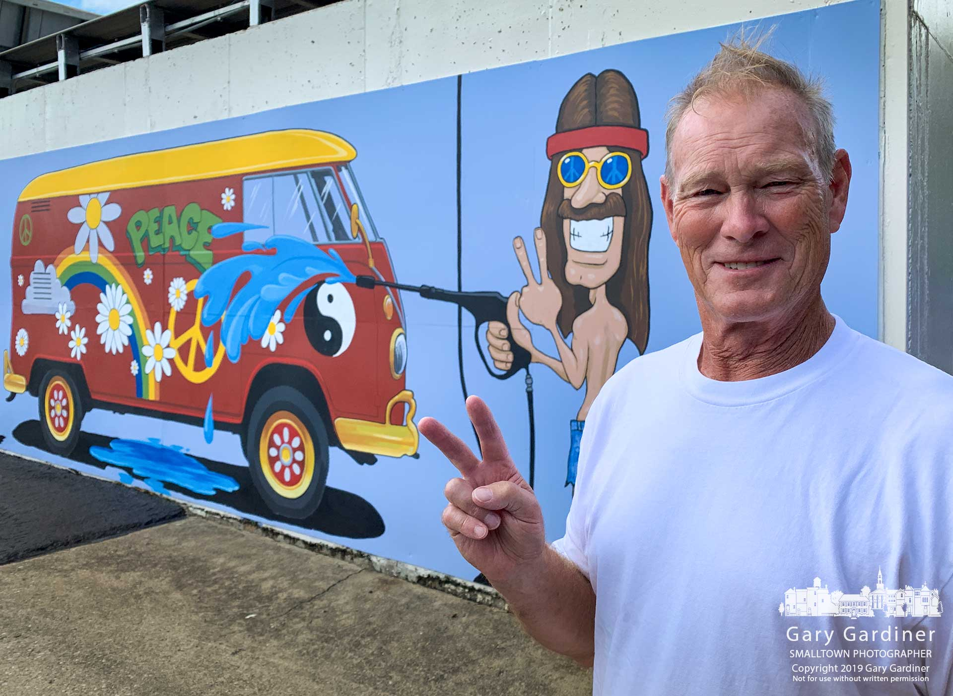 Jim Turner makes a peace sign matching the gesture of the character painted in the mural on the outside of Turner's car wash on North State Street. My Final Photo for Sept. 16, 2019.
