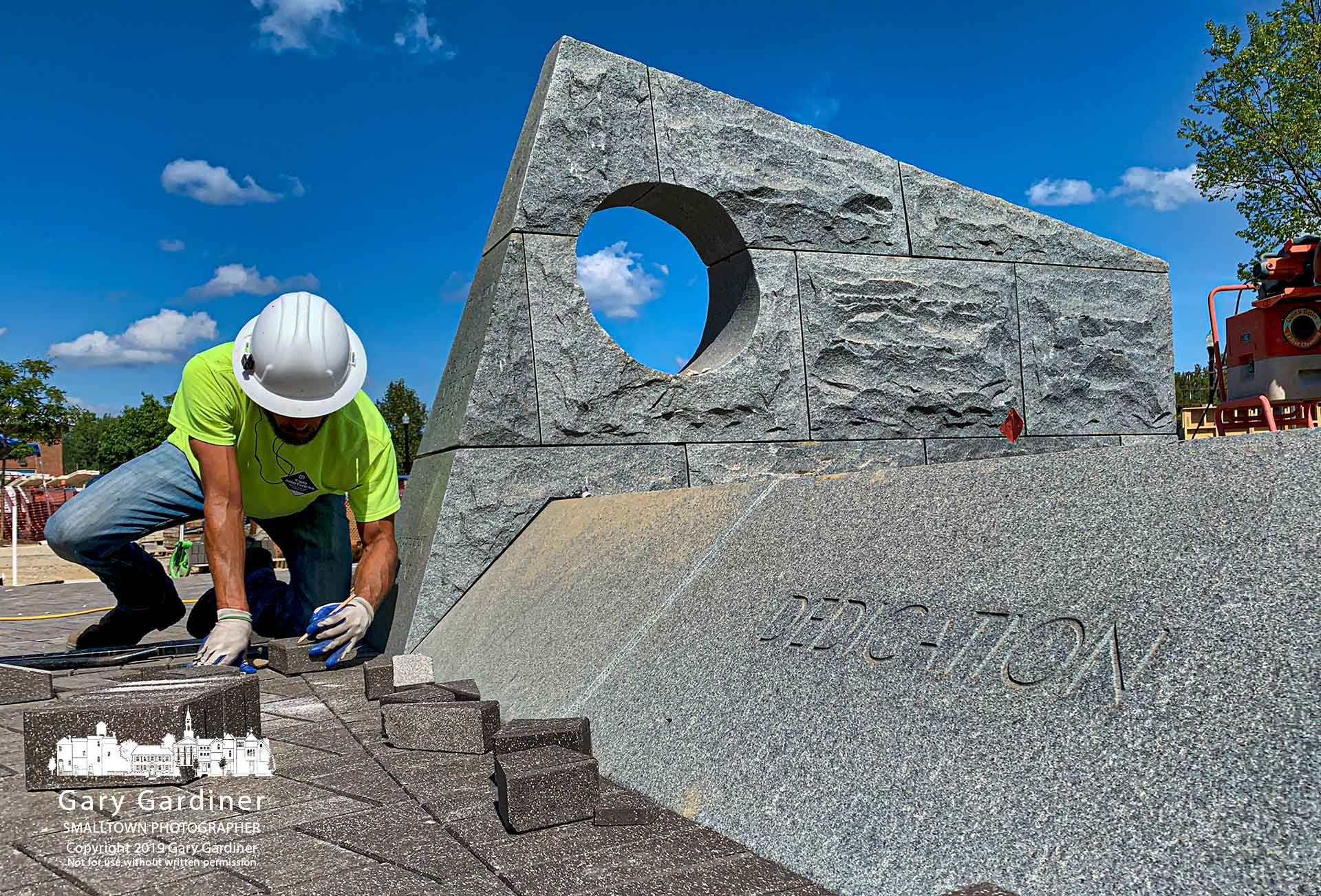 A brick mason measures a cut for one of the pavers being laid in the walkway of First Responders Park on West Main as the contractor continues changes in the park to expand the park and add the names of two police officers killed in the city. My Final Photo for Sept. 17, 2019.