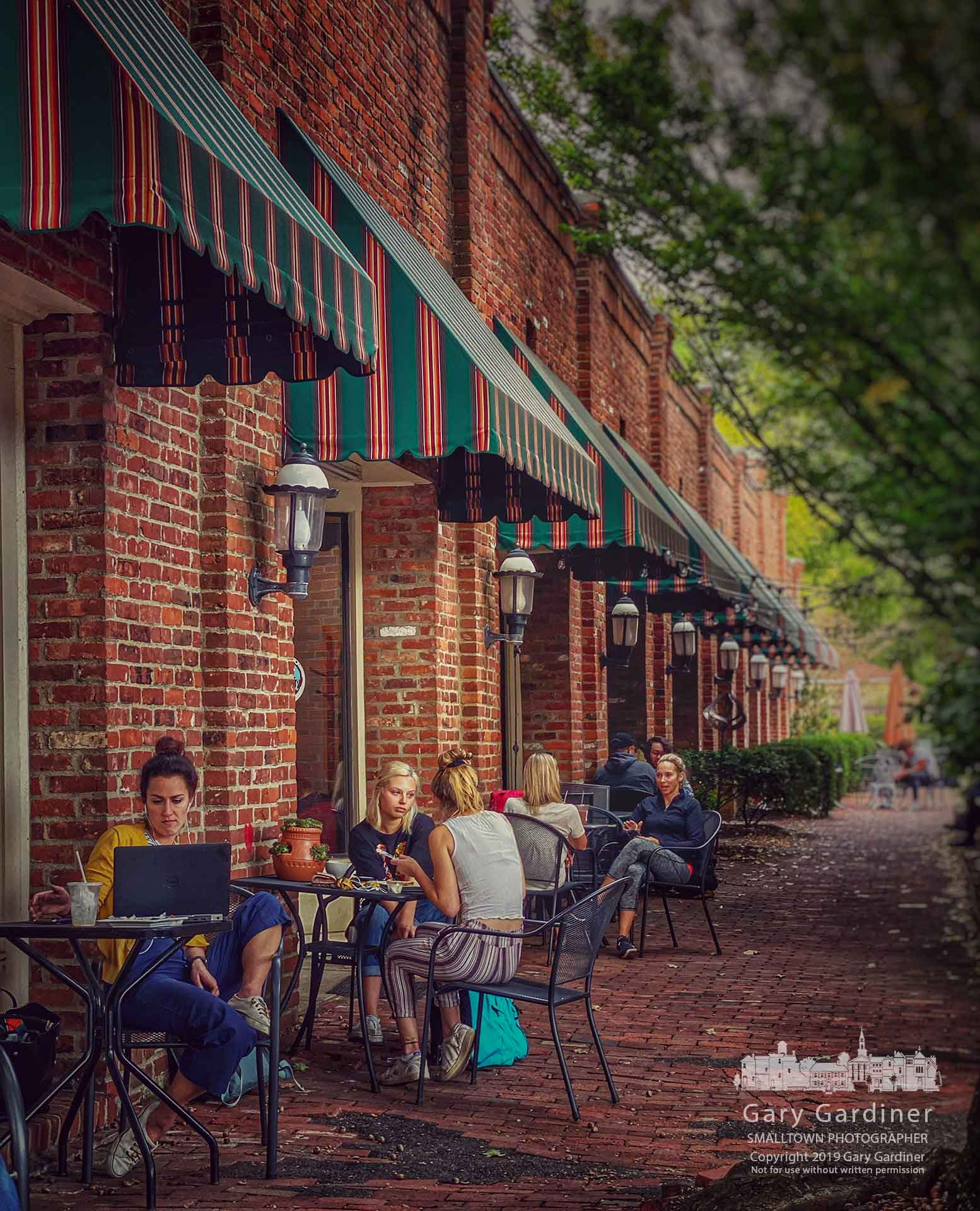 A variety of activities from casual with friends to studying a laptop take place on the brickwalk beside Java Central in Uptown Westerville. My Final Photo for sept. 24, 2019.