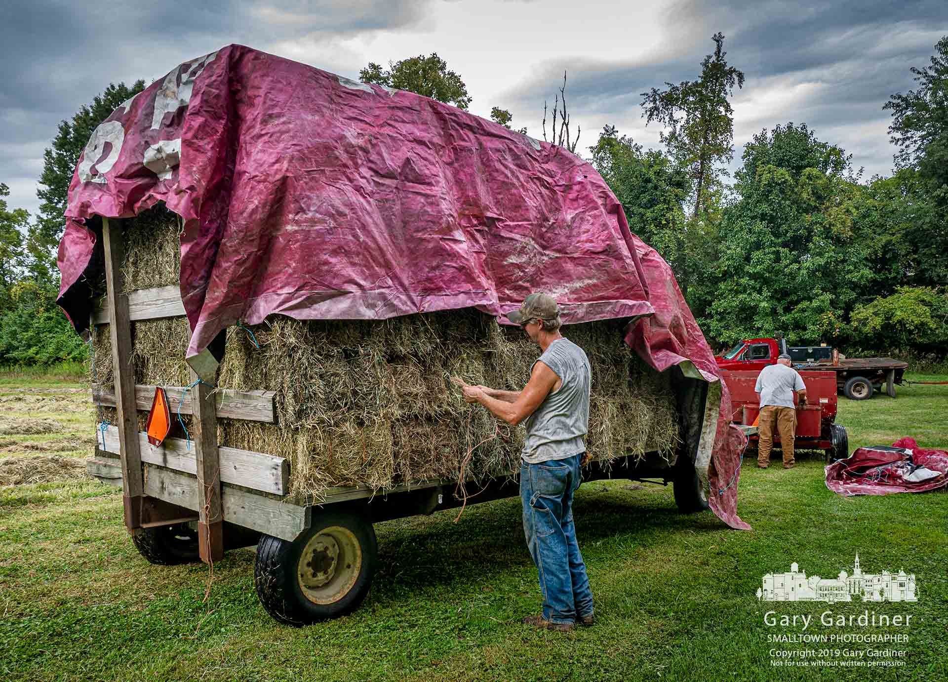 Rodney Parker attaches a tarpaulin to a partial load of hay after an unexpected rain cloud stopped the harvest at a field on North West Street. My Final Photo for Sept. 6, 2019.