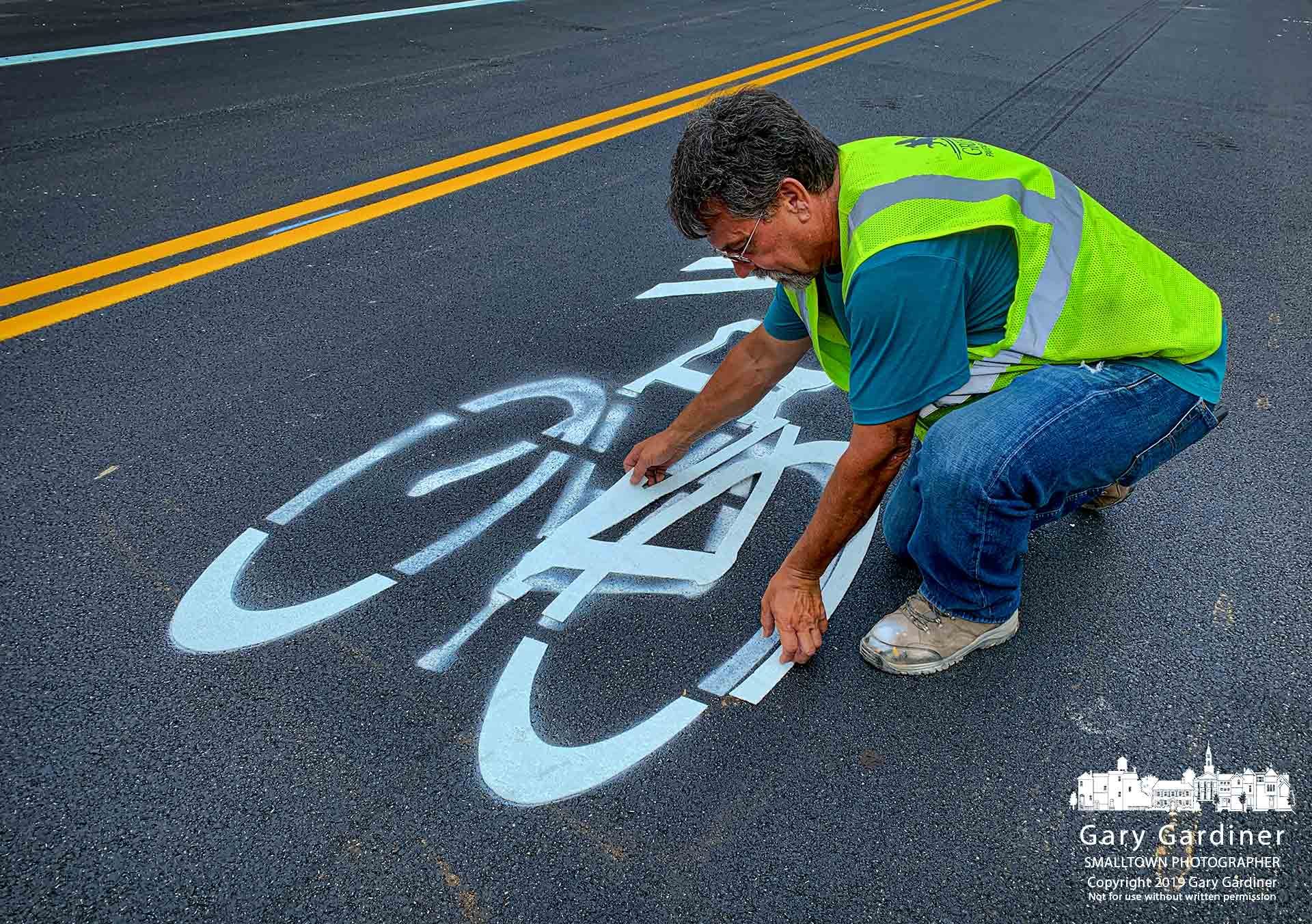A worker places section of plasticized paint strips in the shape of a bicycle in the northbound lane of McCorkle Blvd. as the construction worked to reopen the street before the commuter rush at the end of the day. My Final Photo for Sept. 13, 2019.