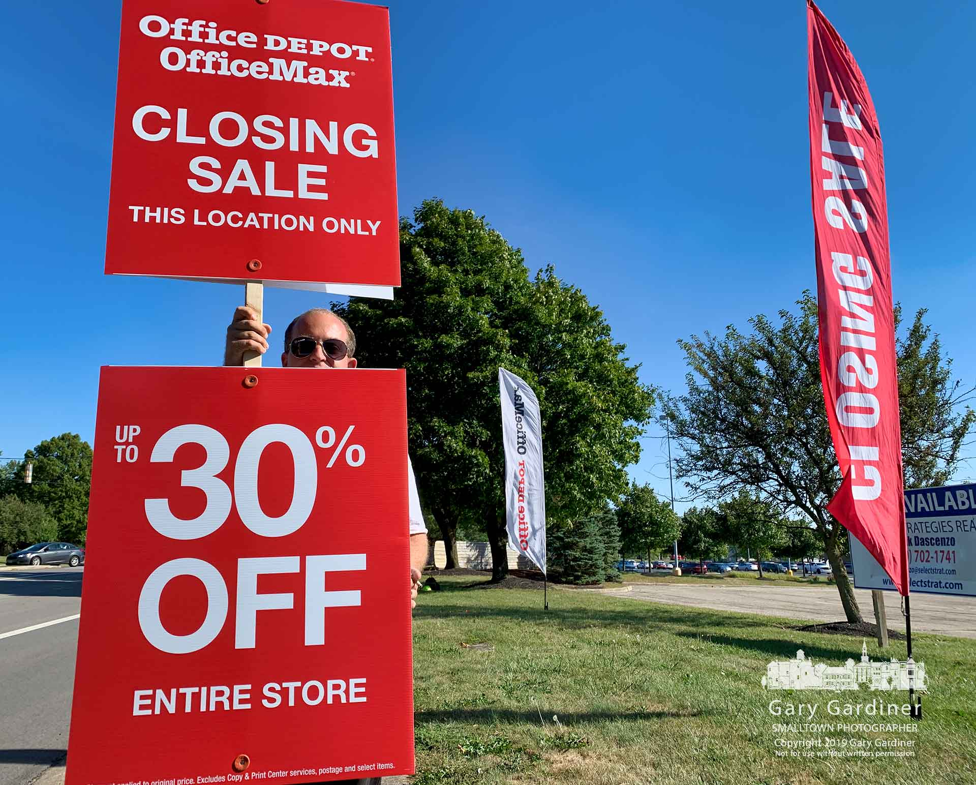 A set of signs noting the closing of the OfficeMax store at Huber and State is held aloft by a store employee Sunday afternoon. My Final Photo for Sept. 22, 2019.