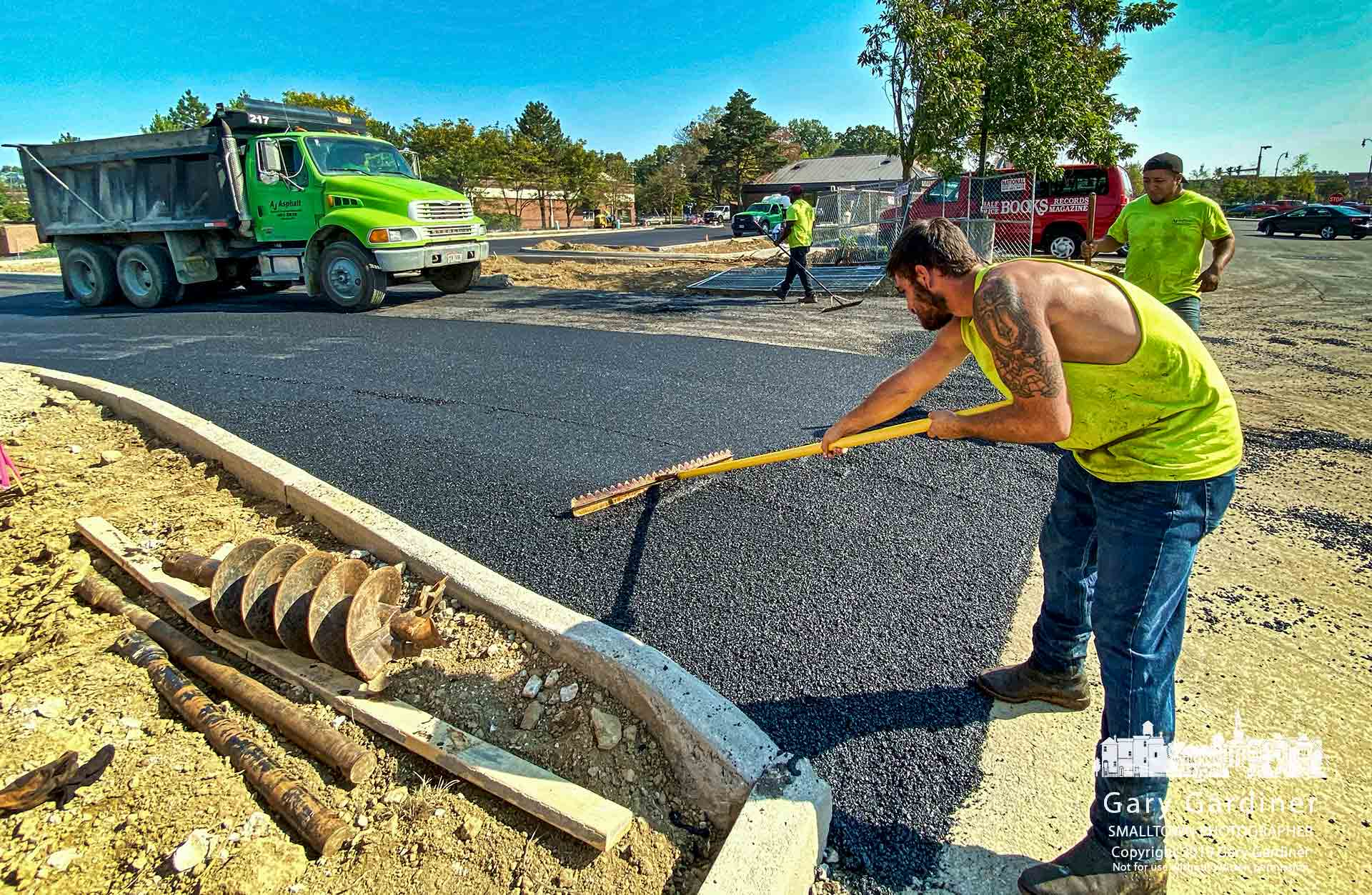 A worker levels a section of freshly poured asphalt at the entrance to what will be the new drive-thru lane for Starbucks on South State Street. My Final Photo for Sept. 30, 2019.