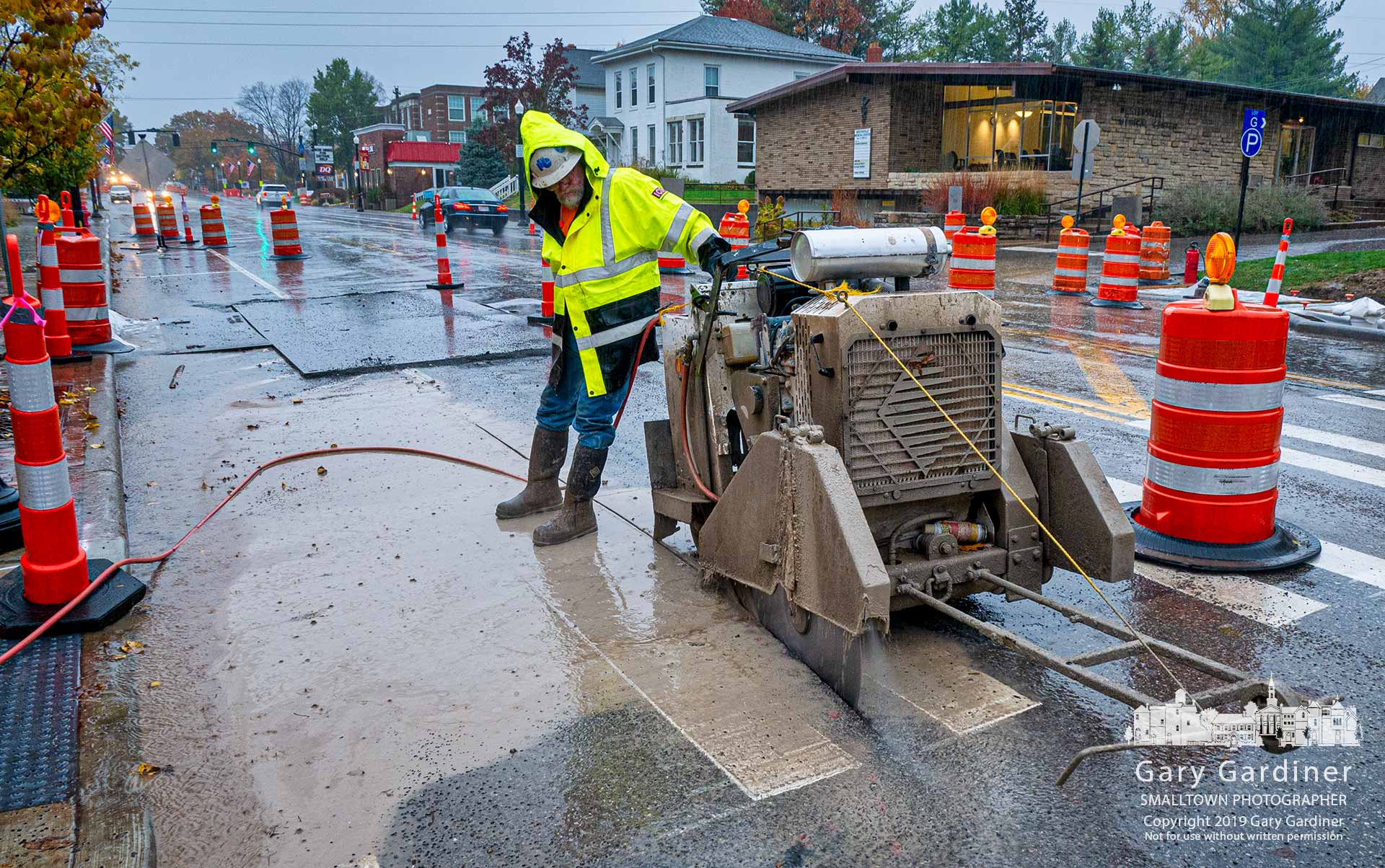 A crew works during the morning rain to cut away sections of South State and the adjacent sidewalk for what will become a bumpout for the rebuilt pedestrian crossing at the library. My Final Photo for Oct. 31, 2019.