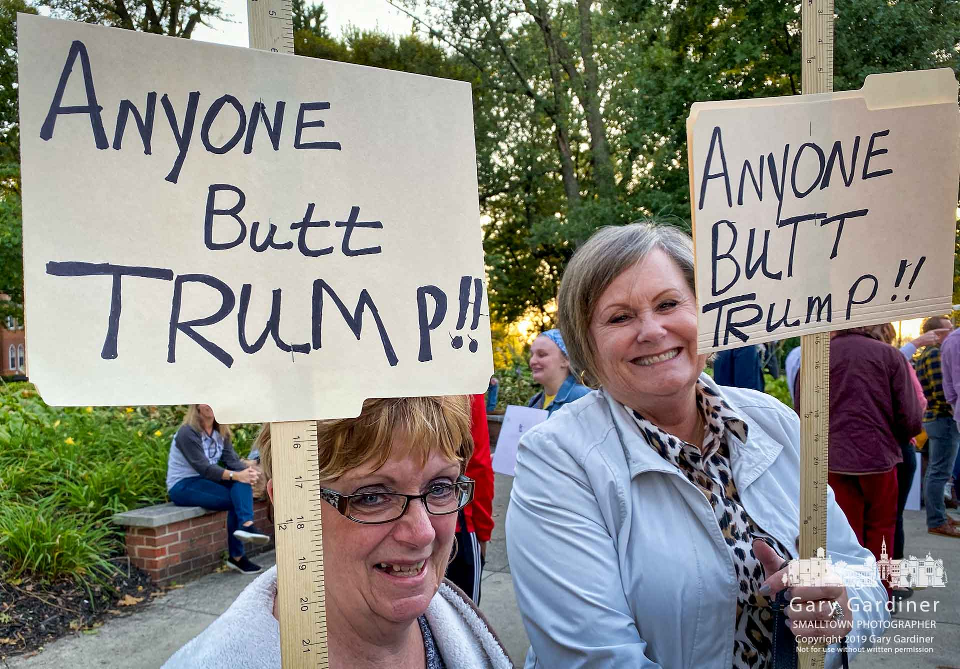 Two women carrying homemade protest signs built from file folders, markers, staples, and yardsticks stand at Grove and West Main before the start of the Democratic presidential debate in Westerville. My Final Photo for Oct. 15, 2019.