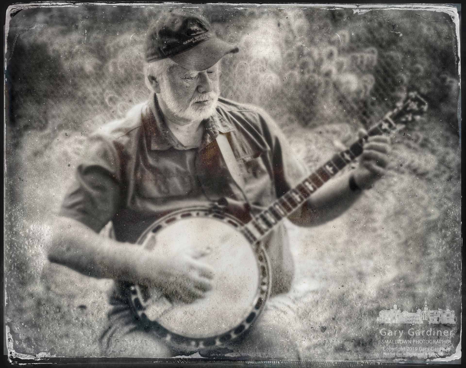 Westerville musician and instructor Gary Puckett plays his banjo near the log cabin during the Ned Mosher Apple Butter Festival at McVay Elementary. My Final Photo for Oct. 6, 2019.