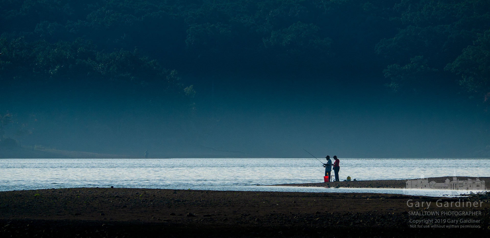 A couple sharing fishing poles stand on the end of a small spit of land at Hoover Reservoir exposed by receding water as the lake level is lowered in the fall. My Final Photo for Oct. 1, 2019.