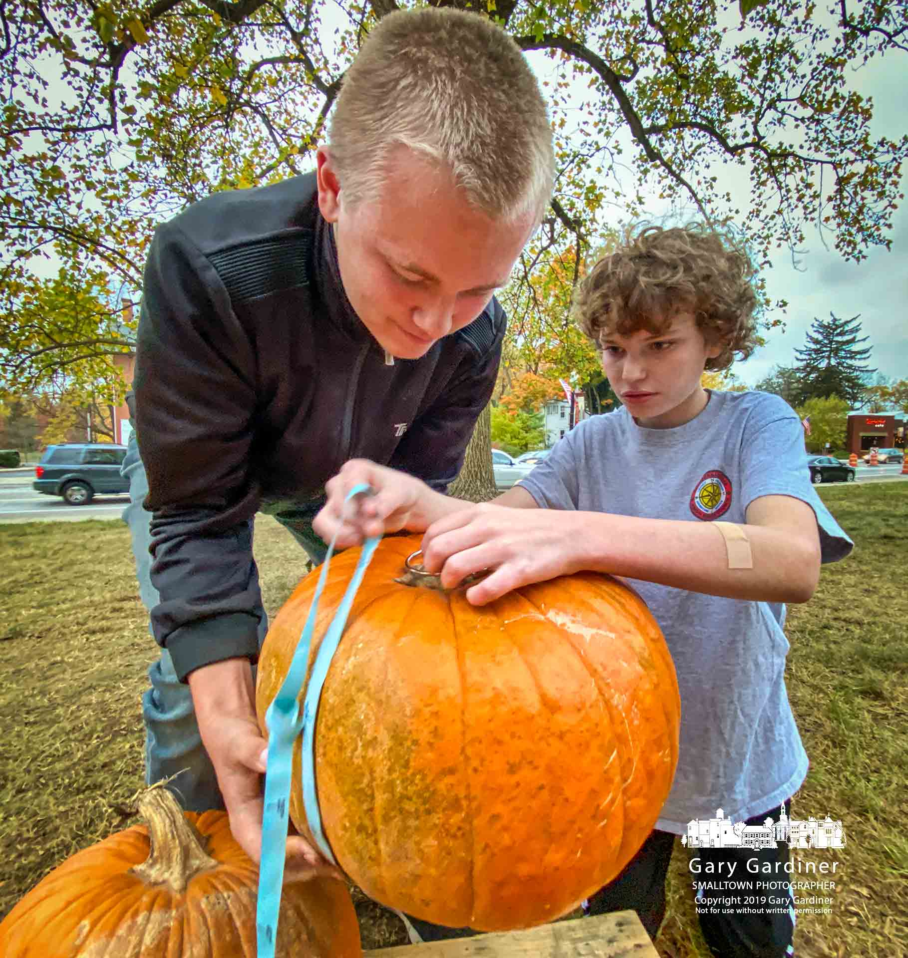 A pair of Boy Scouts measure one of the last pumpkins sold at Troop 560's Pumpkin Patch in front of the Mason Hall in Uptown Westerville. My  Final Photo for October 29, 2019.