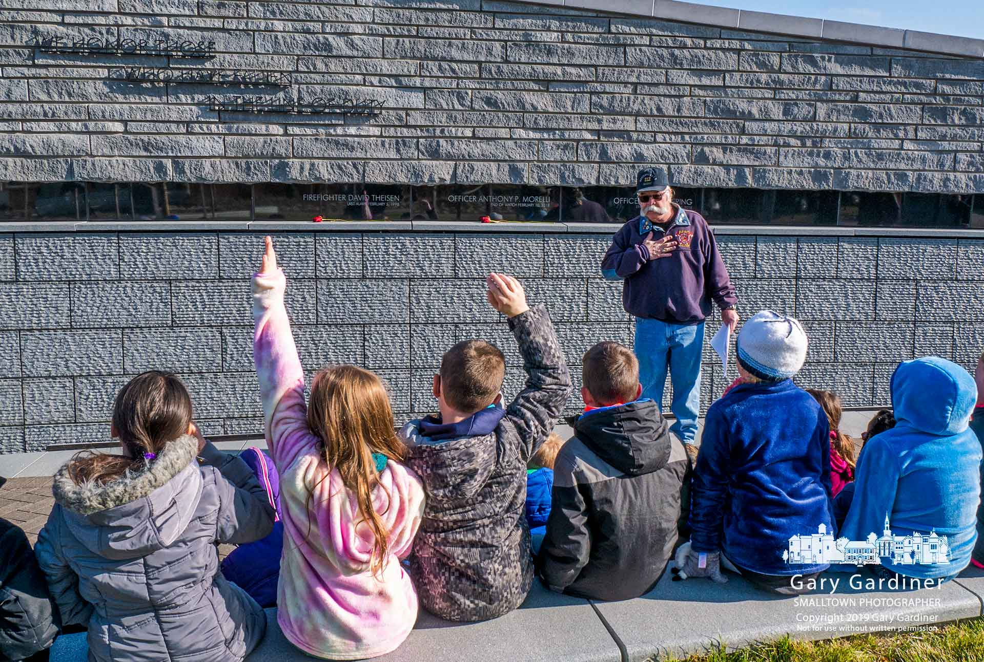 Retired Westerville firefighter Tom Ullom gestures as he completes explaining the park to three classes of students from Emerson Elementary at the end of their visit to First Responders Park on Main Street. My Final Photo for Nov. 20, 2019.