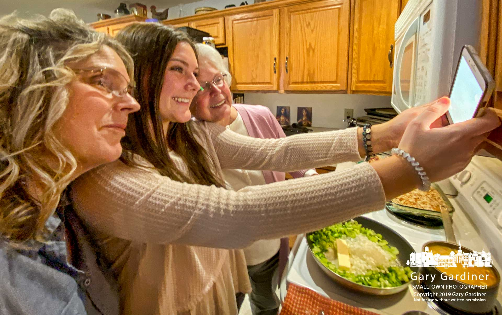 Three of the women in the Gardiner and Robbins families pose for a selfie while cooking vegetables for the stuffing and finishing the seasoning of gravy for Thanksgiving dinner. My Final Photo for Nov. 28, 2019.