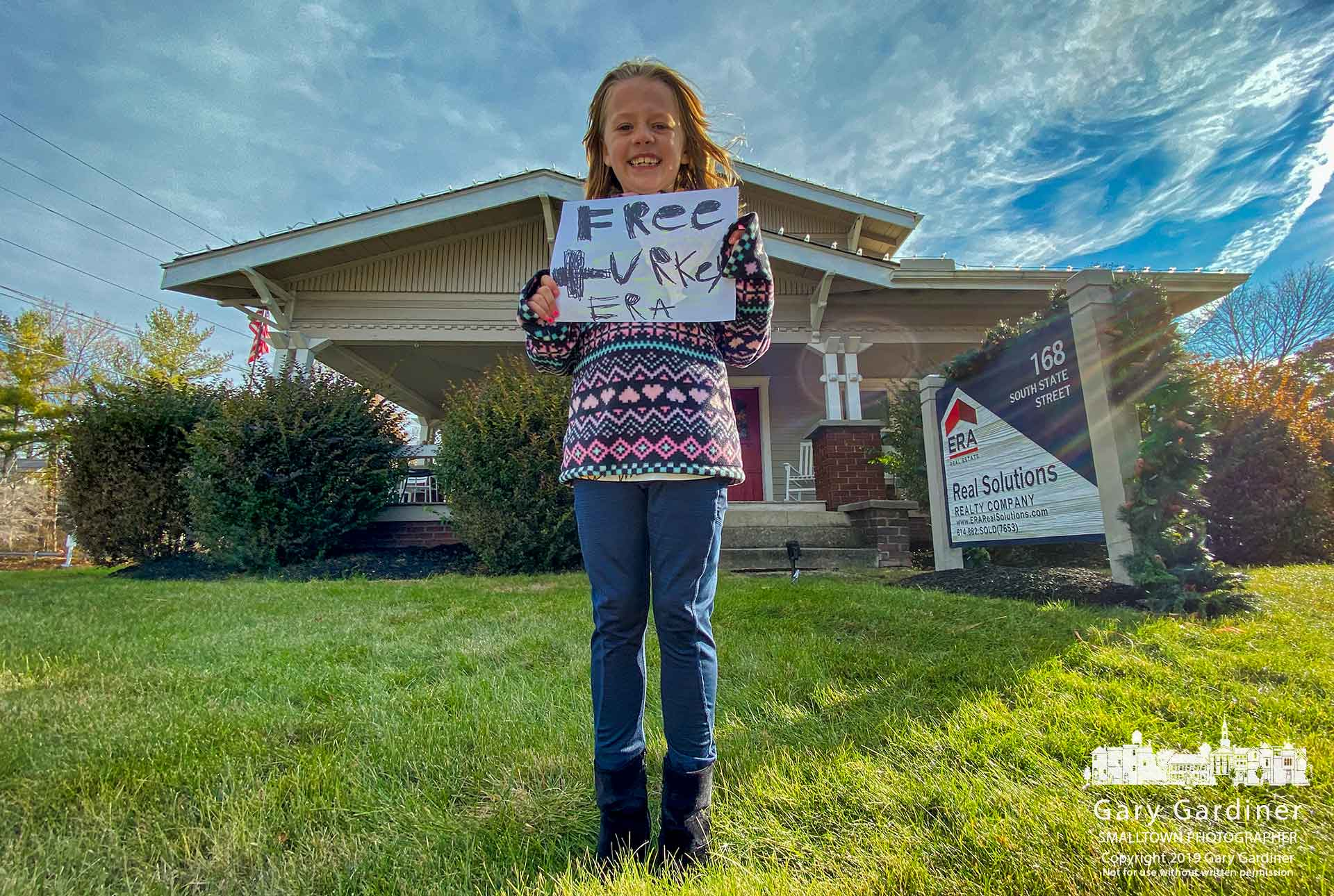 A young girl holds her hand-lettered sign where she advertised free turkeys for people dropping off four cans of food for W.A.R.M. at the ERA Realty office on South State Street. My Final Photo for Nov. 23, 2019.