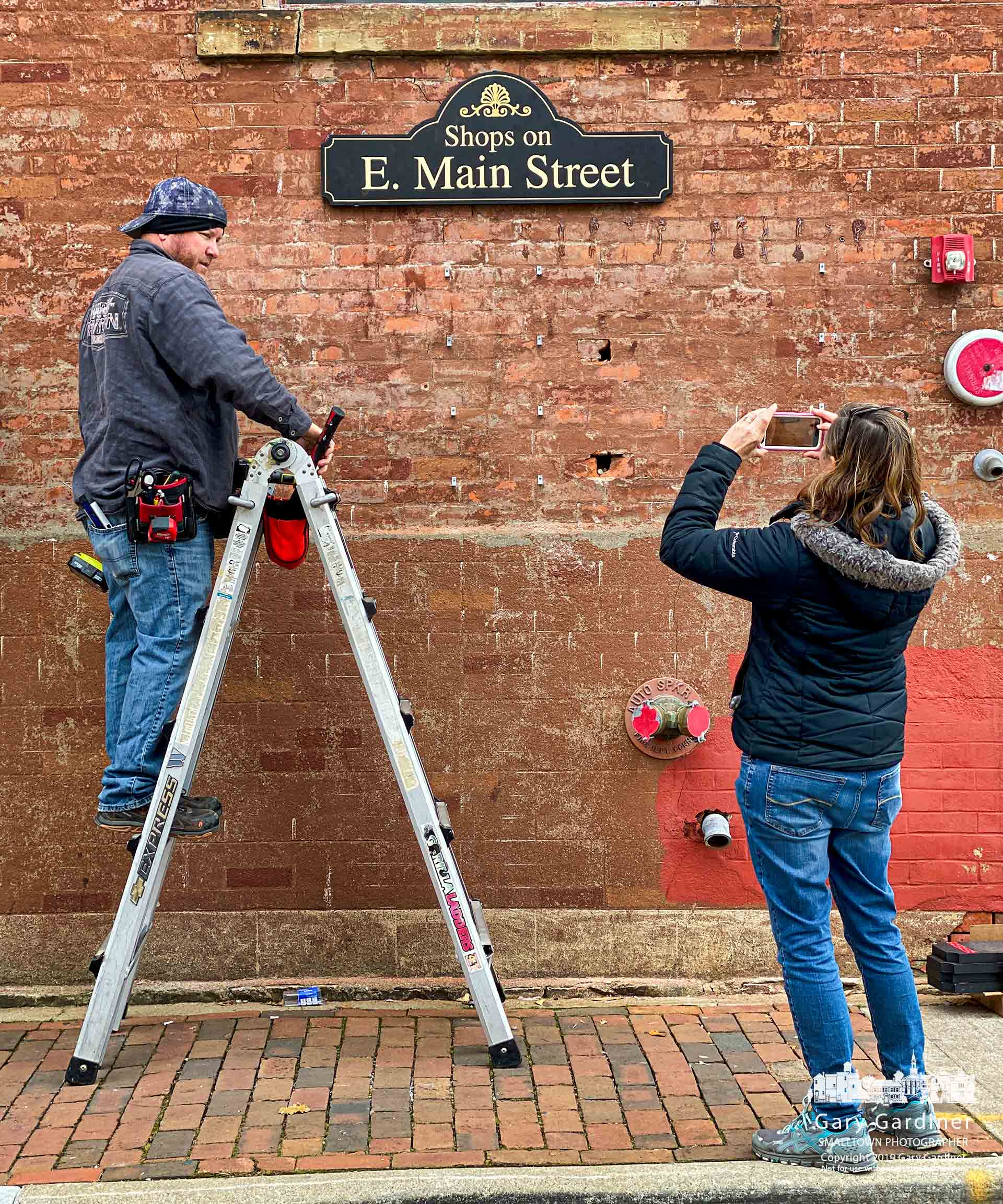 A set of signs noting the businesses on East Main Street are attached to the side of the Old Bag o' Nails building at State Street creating wayfaring notices for people headed south on State. My Final Photo for Nov. 21, 2019.