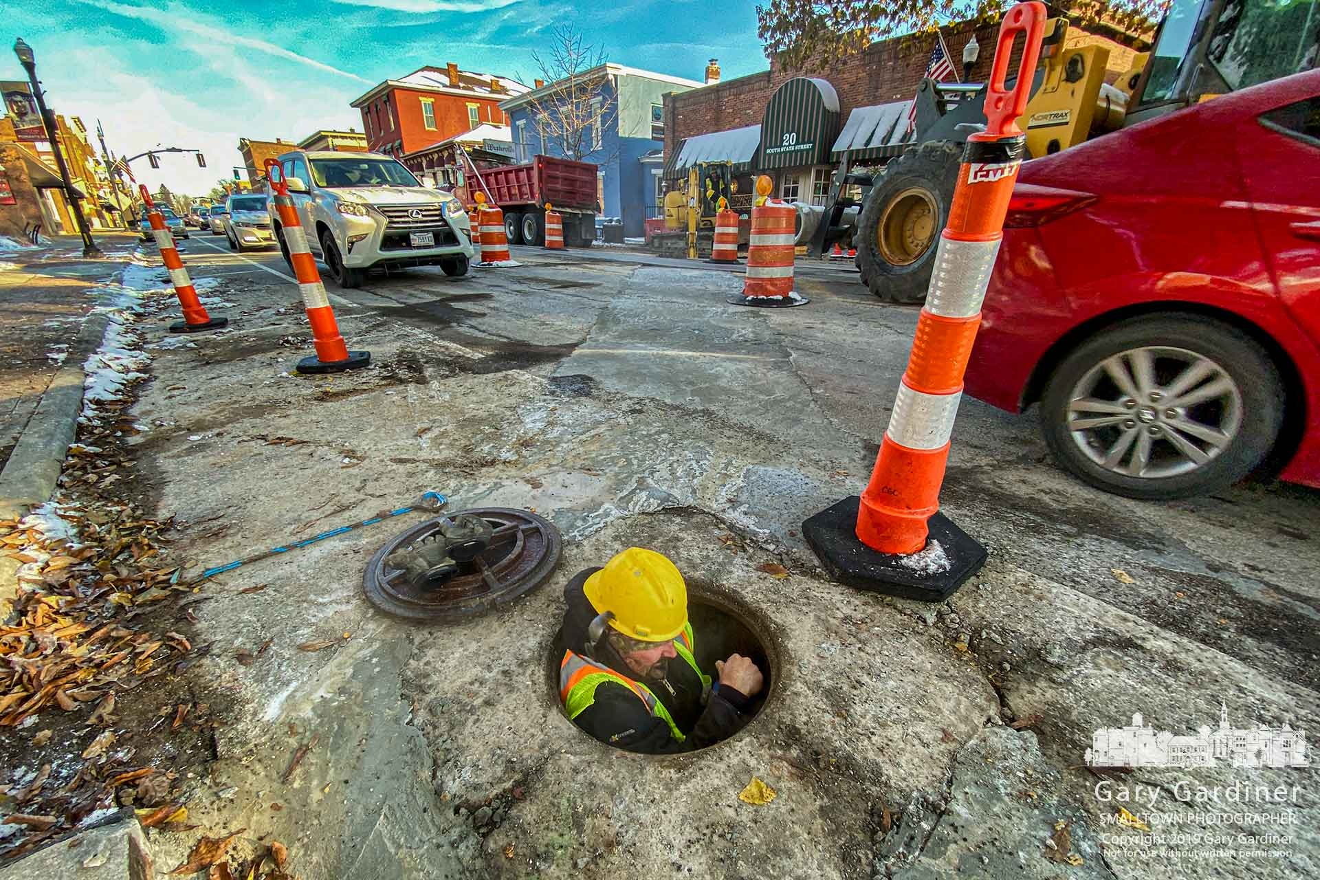 A worker lowers himself into the sewer in front of city hall to place a laser system to measure the proper alignment for a connecting a new sewer line to the main sewer in front of Java Central. My Final Photo for Nov. 13, 2019
