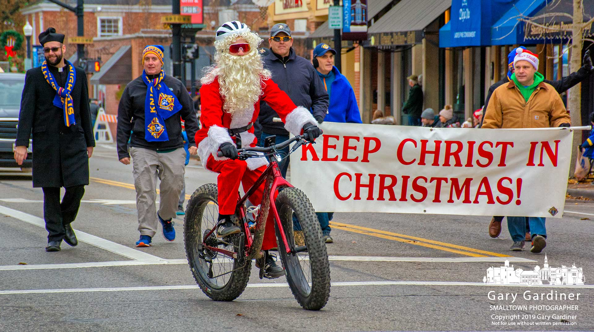 A helmeted Santa Claus rides his big-wheel bike in the Christmas parade leading the way for the Knights of Columbus bearing a banner reminding parade watchers the reason for the season. My Final Photo for Dec. 8, 2019.