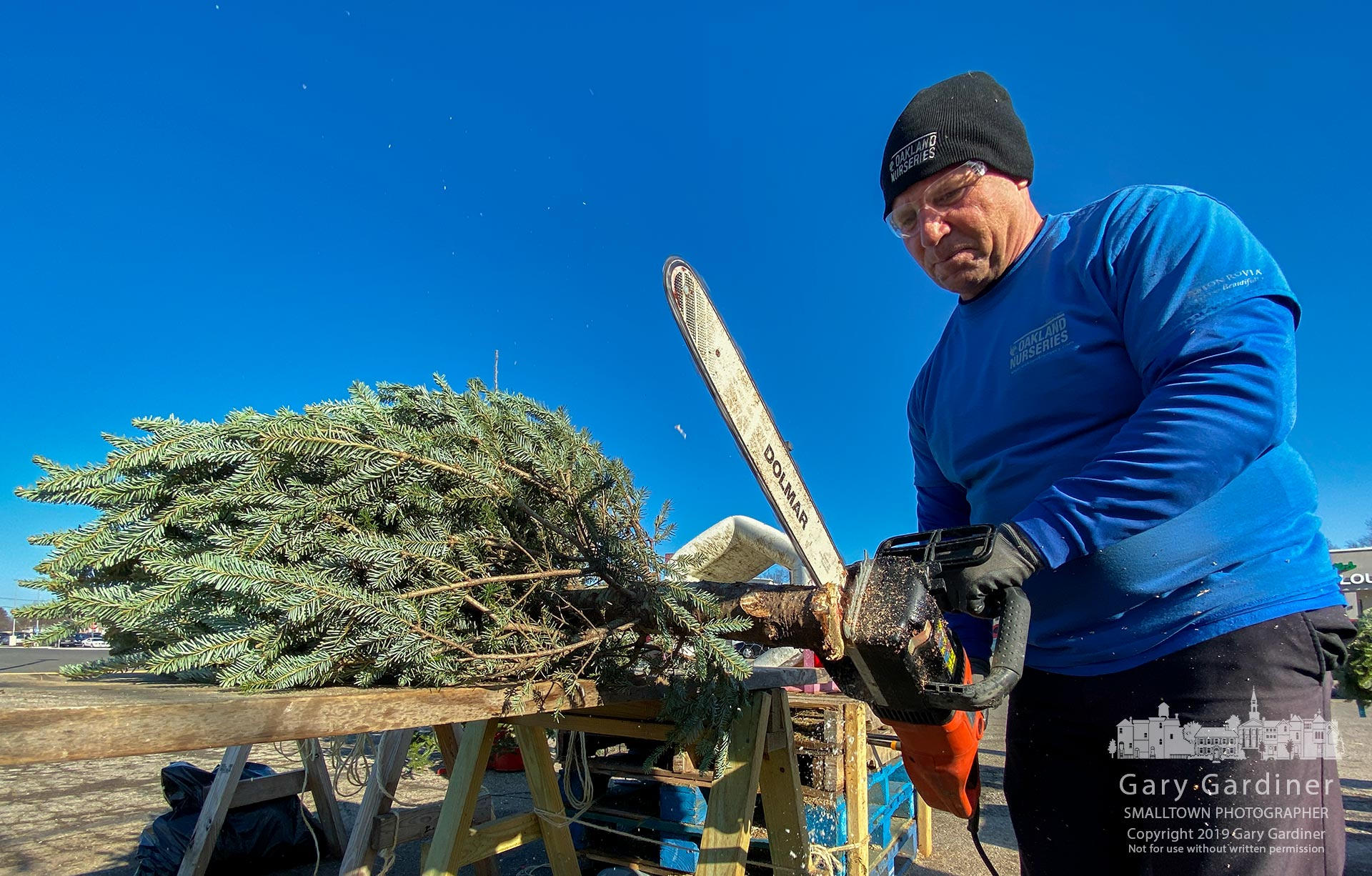 One of the last trees sold at the Glengary Center Christmas Tree lot gets a trim and a shave before being bundled in plastic and tied atop a customer's vehicle. My Final Photo for Dec. 22, 2019.