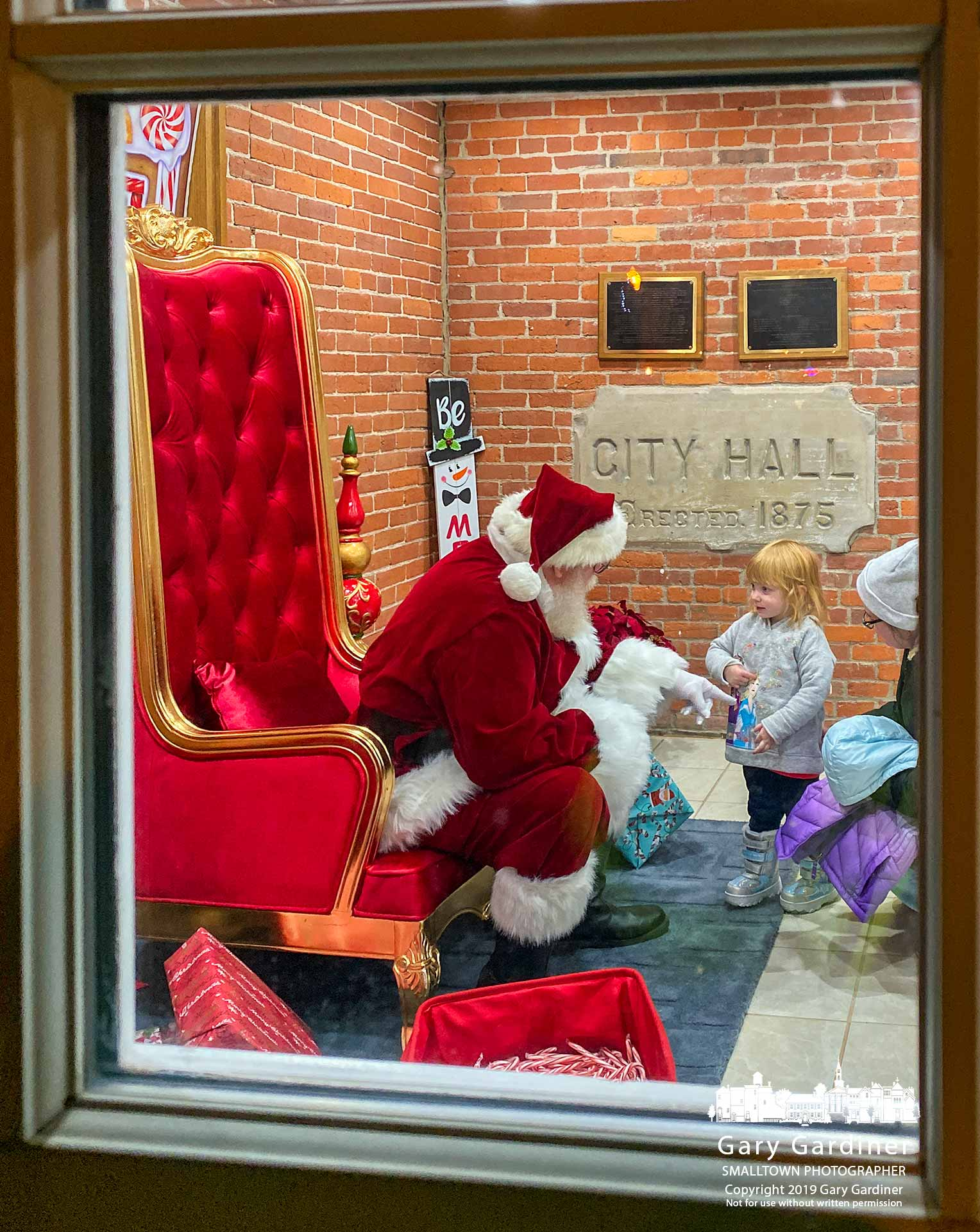 Santa Claus talks with a slightly reluctant young girl as her mother helps take relieve her anxiety about the greeting after waiting in line to see Santa during the Christmas tree lighting ceremony at city hall. My Final Photo for Dec. 6, 2019.