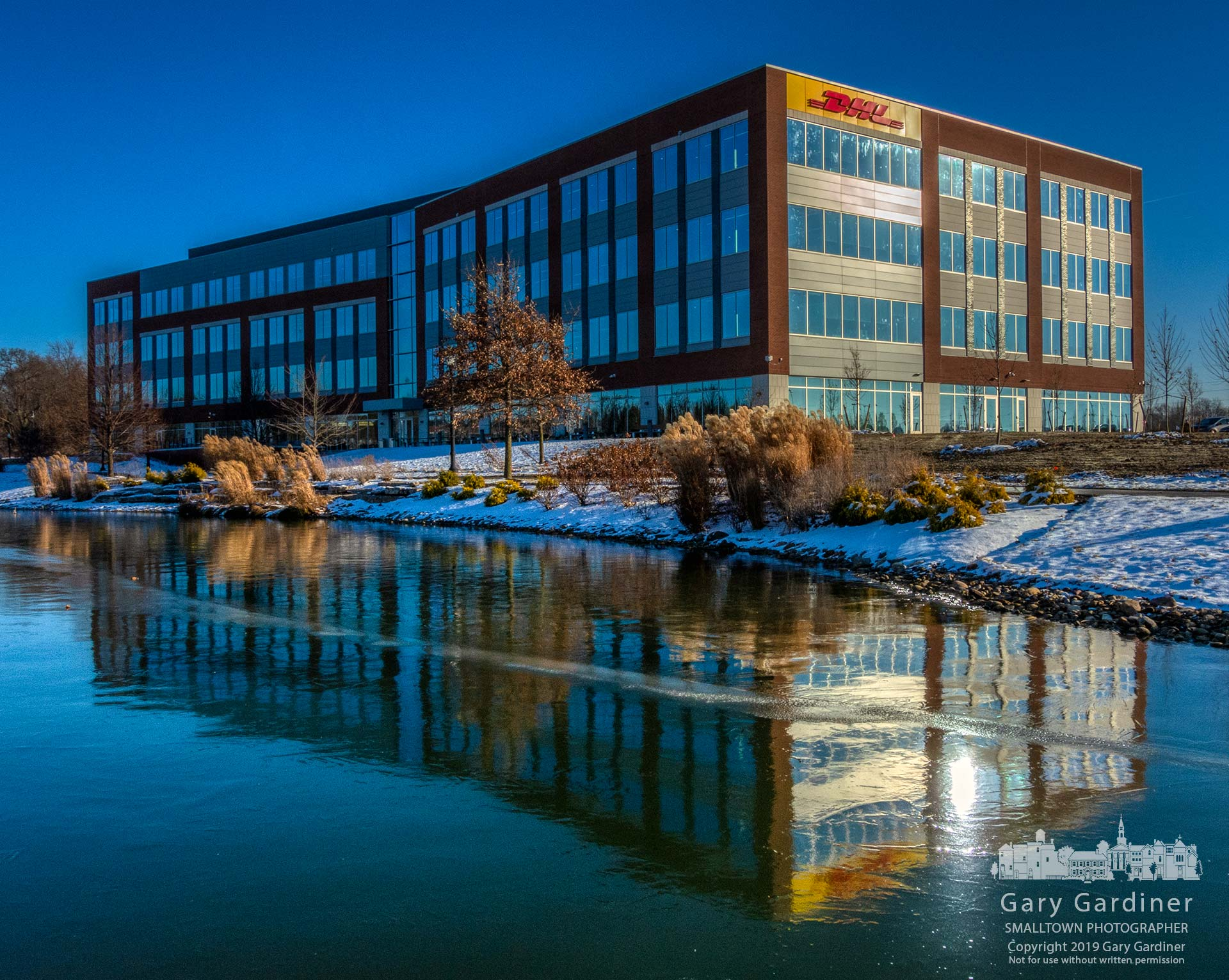 The recently completed DHL Supply Chain North and South America headquarters is reflected in the frozen surface of the pond between it and the Renaissance Hotel. My Final Photo for Dec. 19, 2019.