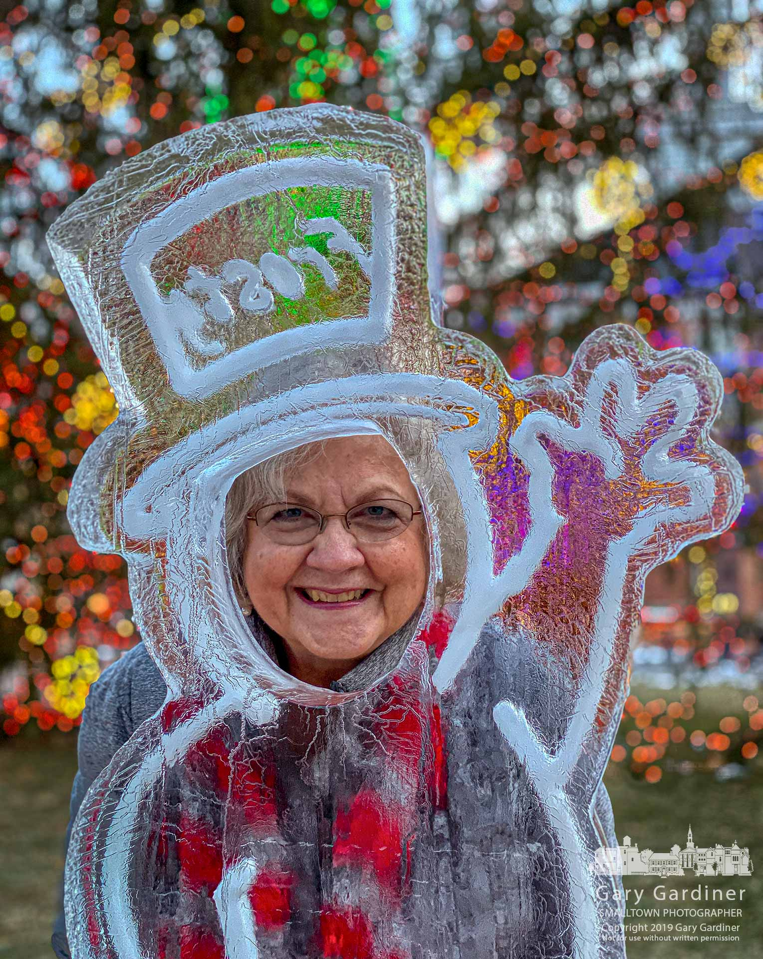 A woman poses with her face in the opening for Frosty the Snowman's ice sculpture in front of the Christmas tree in front of city hall in Uptown Westerville on the weekend before Christmas. My Final Photo for Dec. 20, 2019.