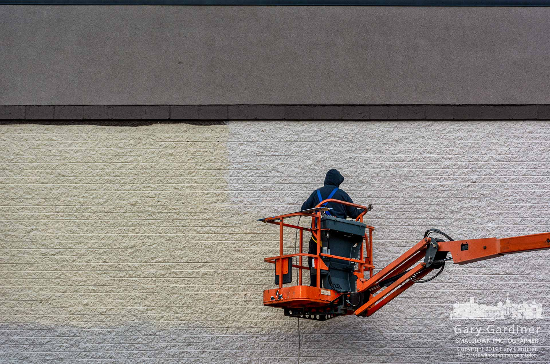 A painter sprays a slightly more neutral color paint on the exterior of the old Office Max building as it is converted to a Planet Fitness health club. My Final Photo for Dec. 12, 2019.