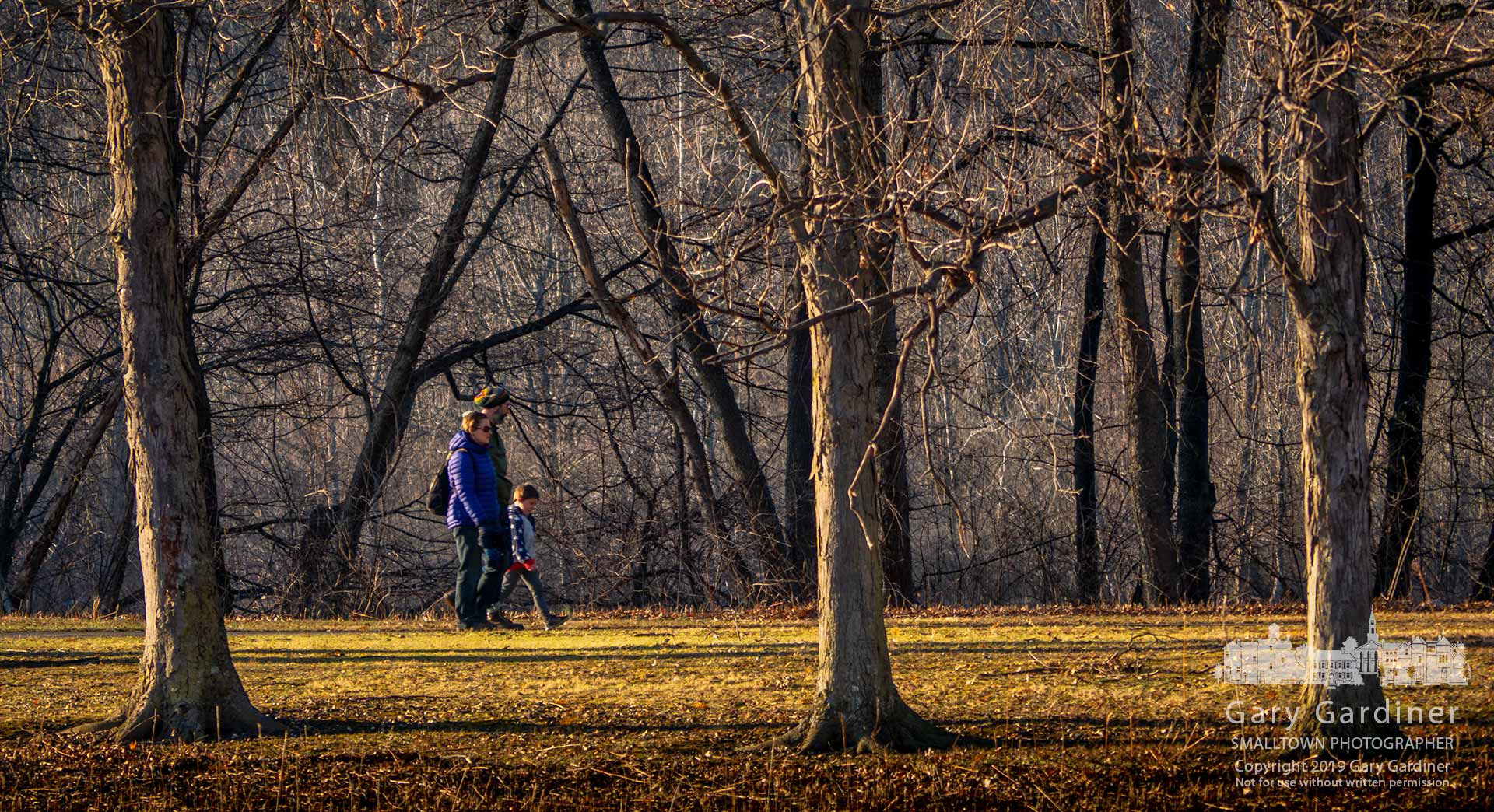 A family walks in the late afternoon sun along a section of the path beside Schrock Lake in Sharon Woods Metro Park. My Final Photo for Dec. 21, 2019.