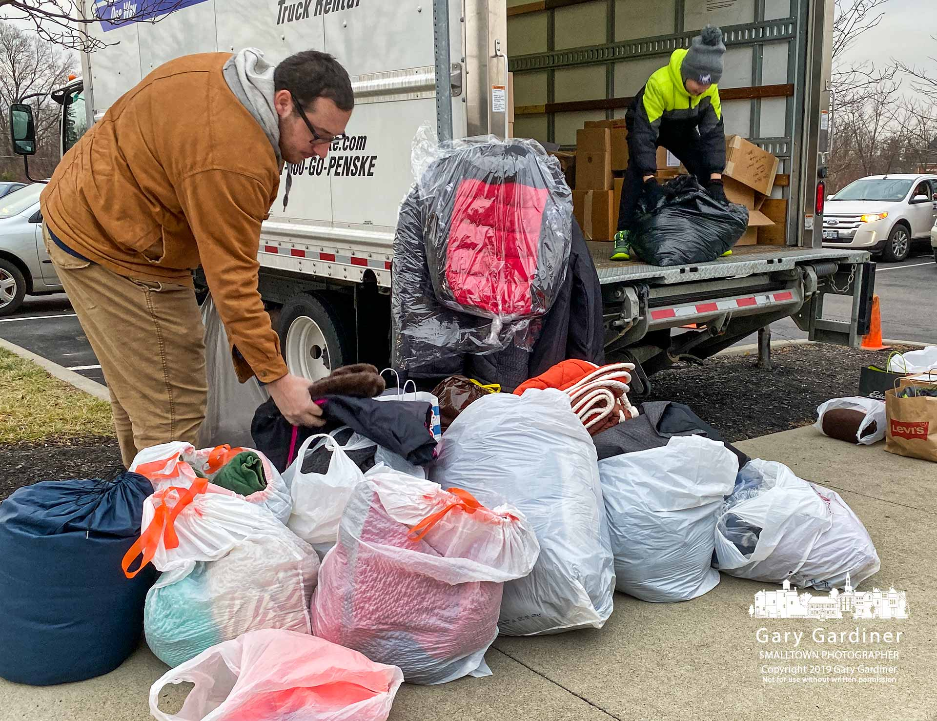 St. Paul the Apostle youth minister Brad Romantic helps sort through the winter coats, blankets, and bedding items donated by parishioners during Sunday Masses. My Final Photo for Dec. 15, 2019.