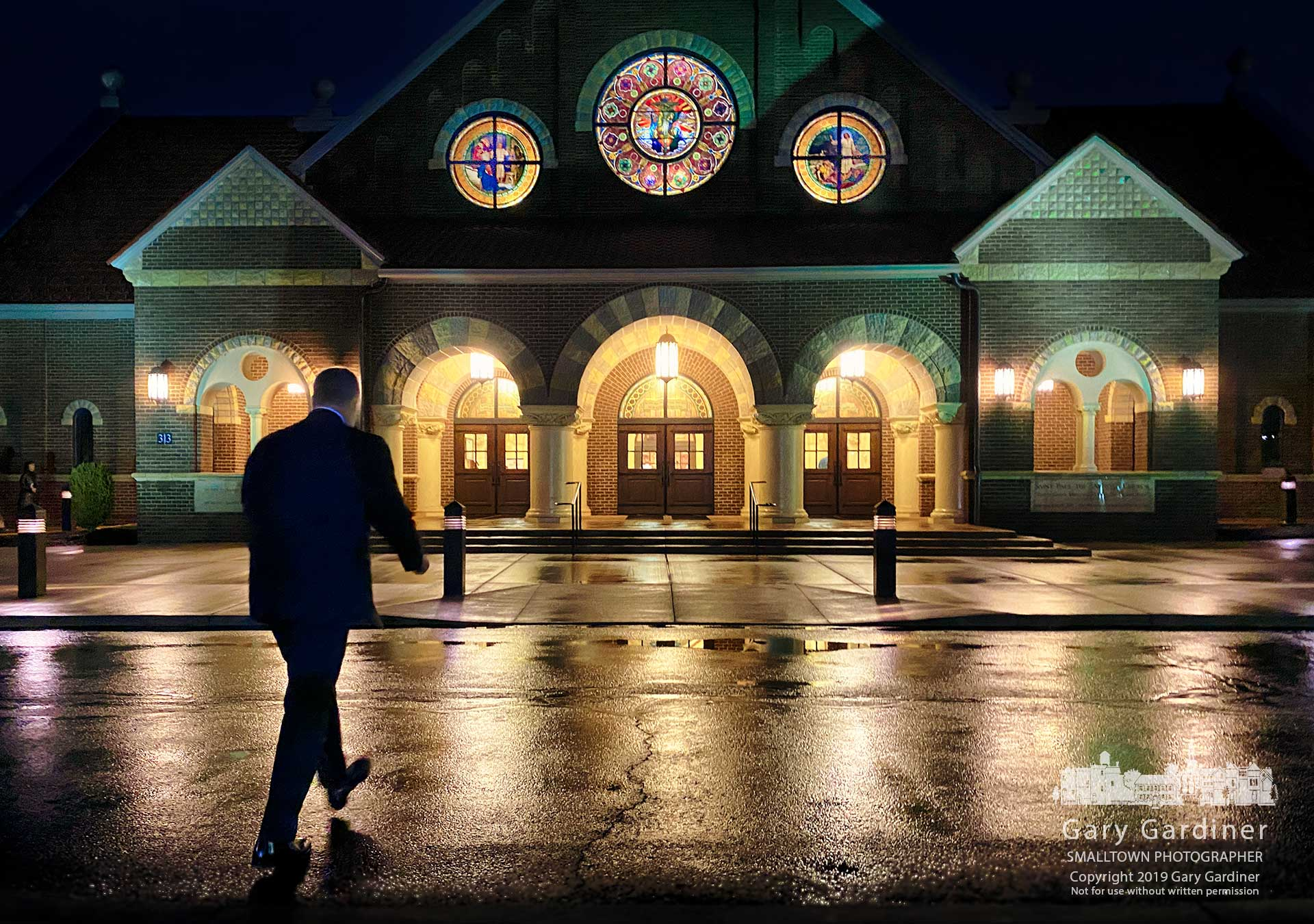 Parishioners arrive before sunrise during an early morning rain for the first Mass at St. Paul the Apostle Church Sunday. My Final Photo for Dec. 29, 2019.