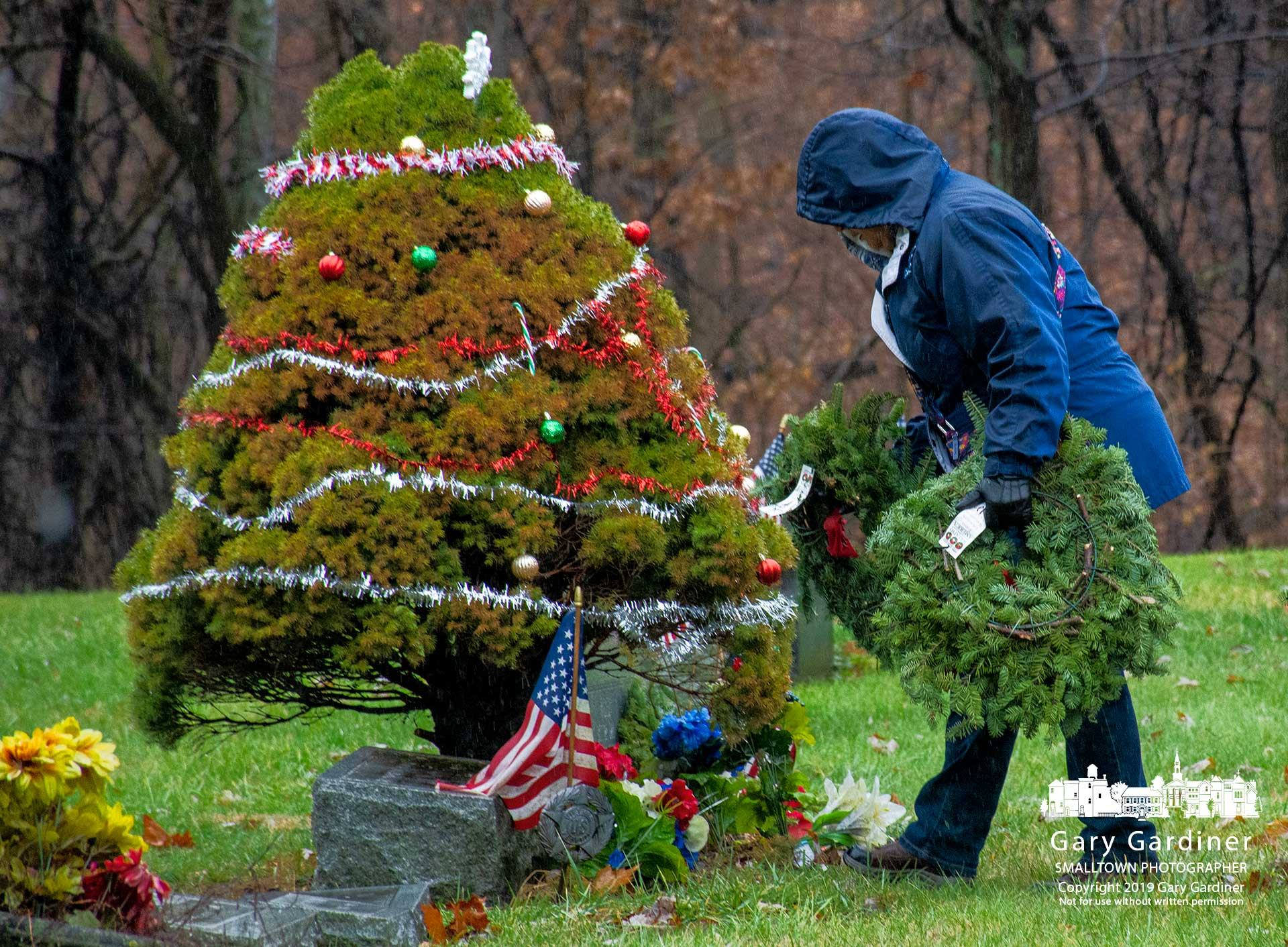 A volunteer places a wreath at the gravestone for Lt. Dingus Banks at Otterbein Cemetery where 520 wreaths were placed as part of Wreaths Across America. My Final Photo for Dec. 15, 2019.