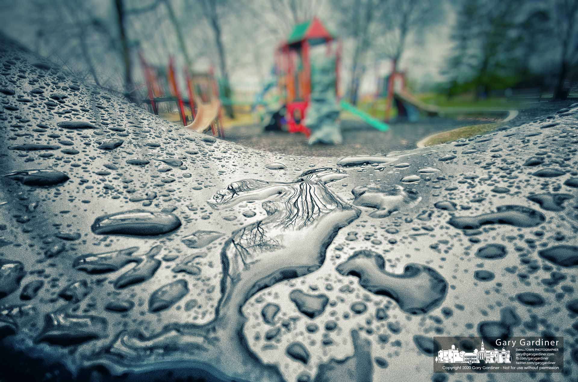 The bare trees surrounding the Alum Creek Park playground are reflected in puddles settling onto one of the seats in a swing at the park after a night and day of rain. My Final Photo for Jan. 24, 2020.