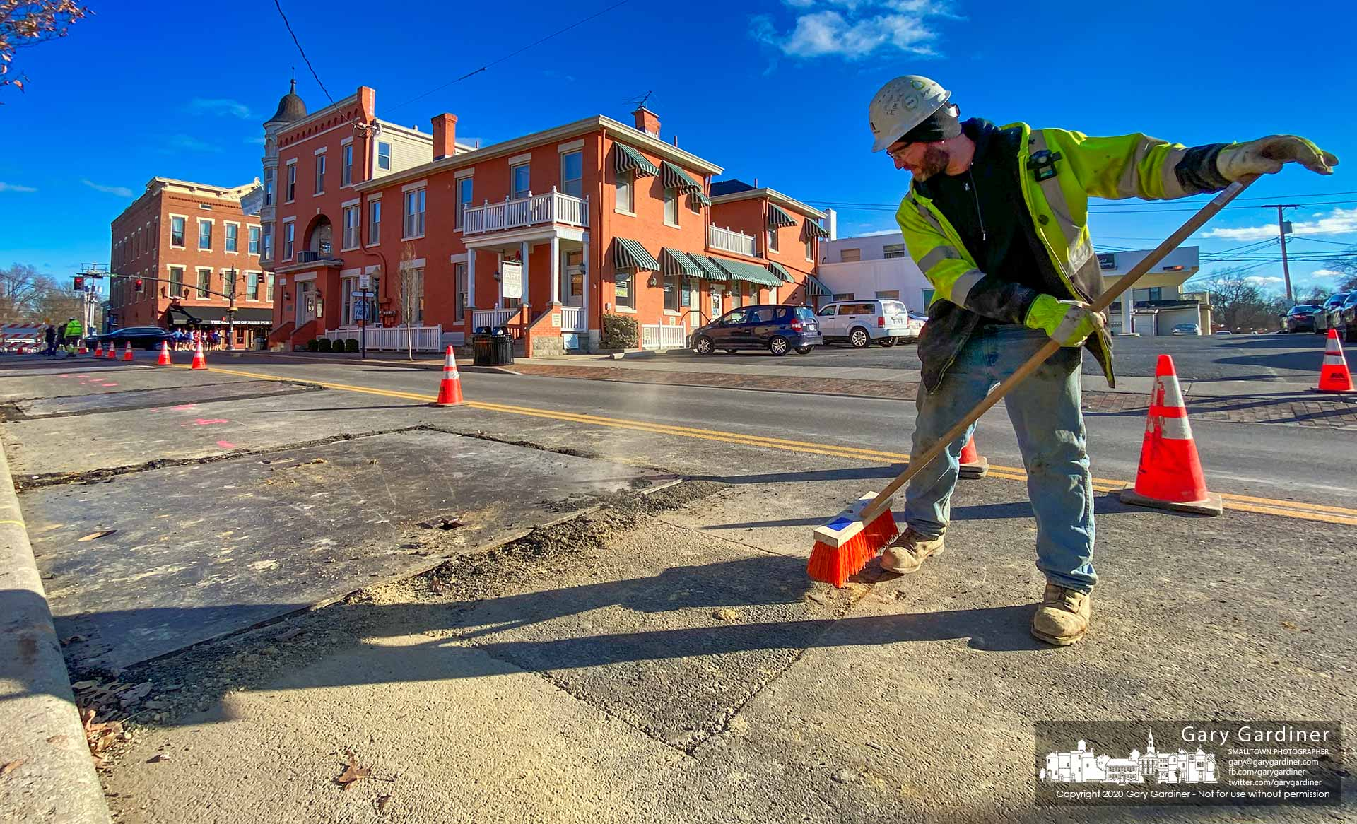 A Miller Pipeline worker sweeps away debris after covering a section of West Main where the company bored a pipeline for Columbia Gas to install new services to the Holmes Hotel, in background, and its businesses in Uptown Westerville. My Final Photo for Jan. 8, 2020.
