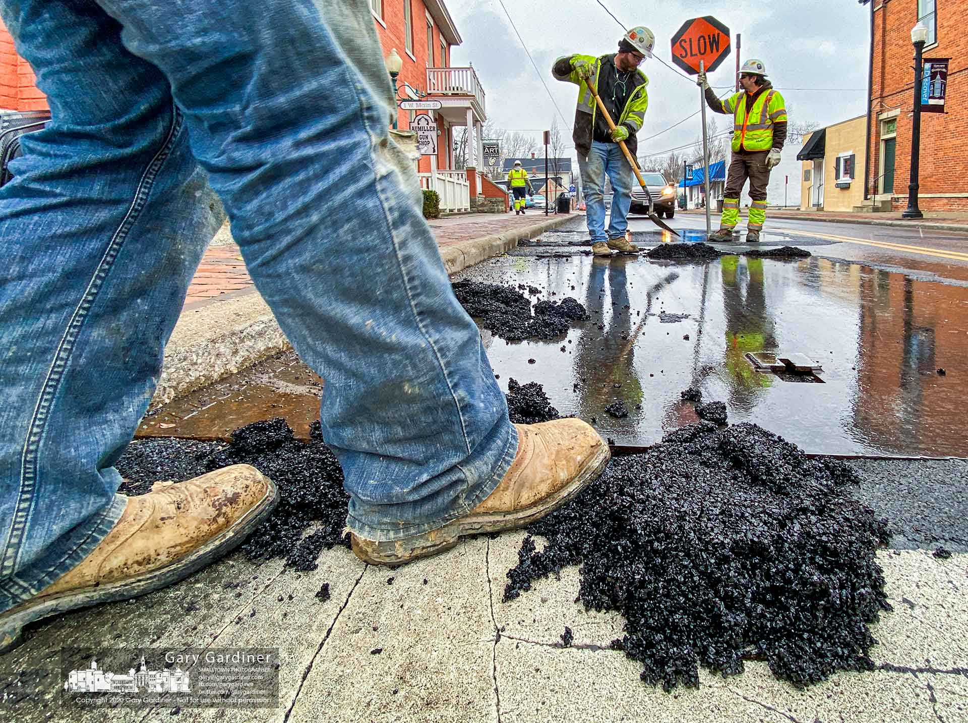 A Miller Pipeline crew presses cold patch asphalt into place around steel plates installed over Columbia Gas Company work holes on West Main Street. My Final Photo for Jan. 31, 2020.