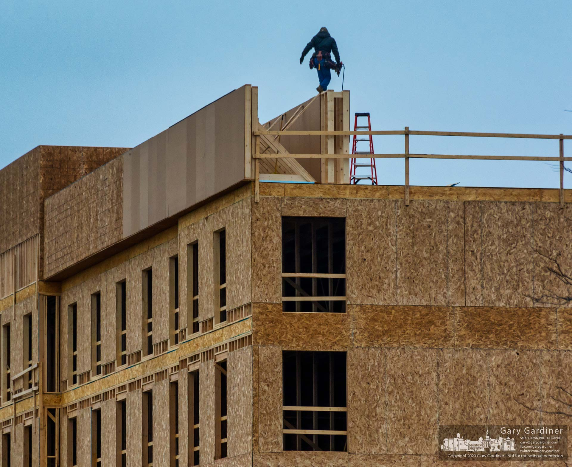 A carpenter steadies himself as he walks across a section of the parapet atop the new Home 2 Suites hotel being built adjacent to Costco near Polaris. My Final Photo for Jan. 27, 2019.