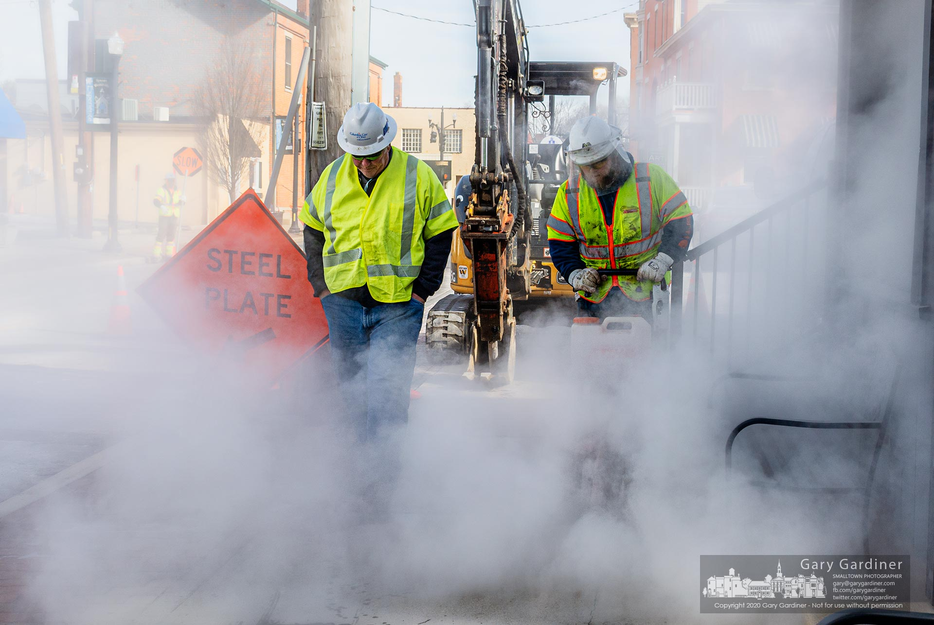 Pipeline workers walk through a cloud of concrete dust as the crew cut away a section of sidewalk while replacing old gas lines in Uptown repaired a patch on West Main Street. My Final Photo for Jan. 22, 2020.