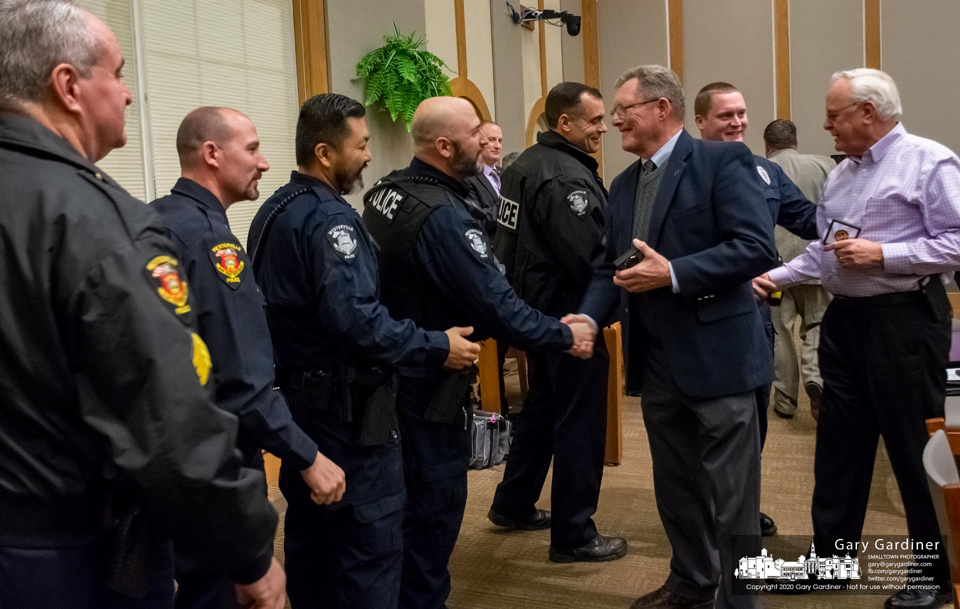 Westerville Police Reserve officers Ted Bretthauer, in blue blazer, and John Clay, right, receive congratulatory handshakes from other officers after the two received commendation coins after retiring from the police force with 80 years of law enforcement experience between the two men. My Final Photo for Jan. 7, 2020.