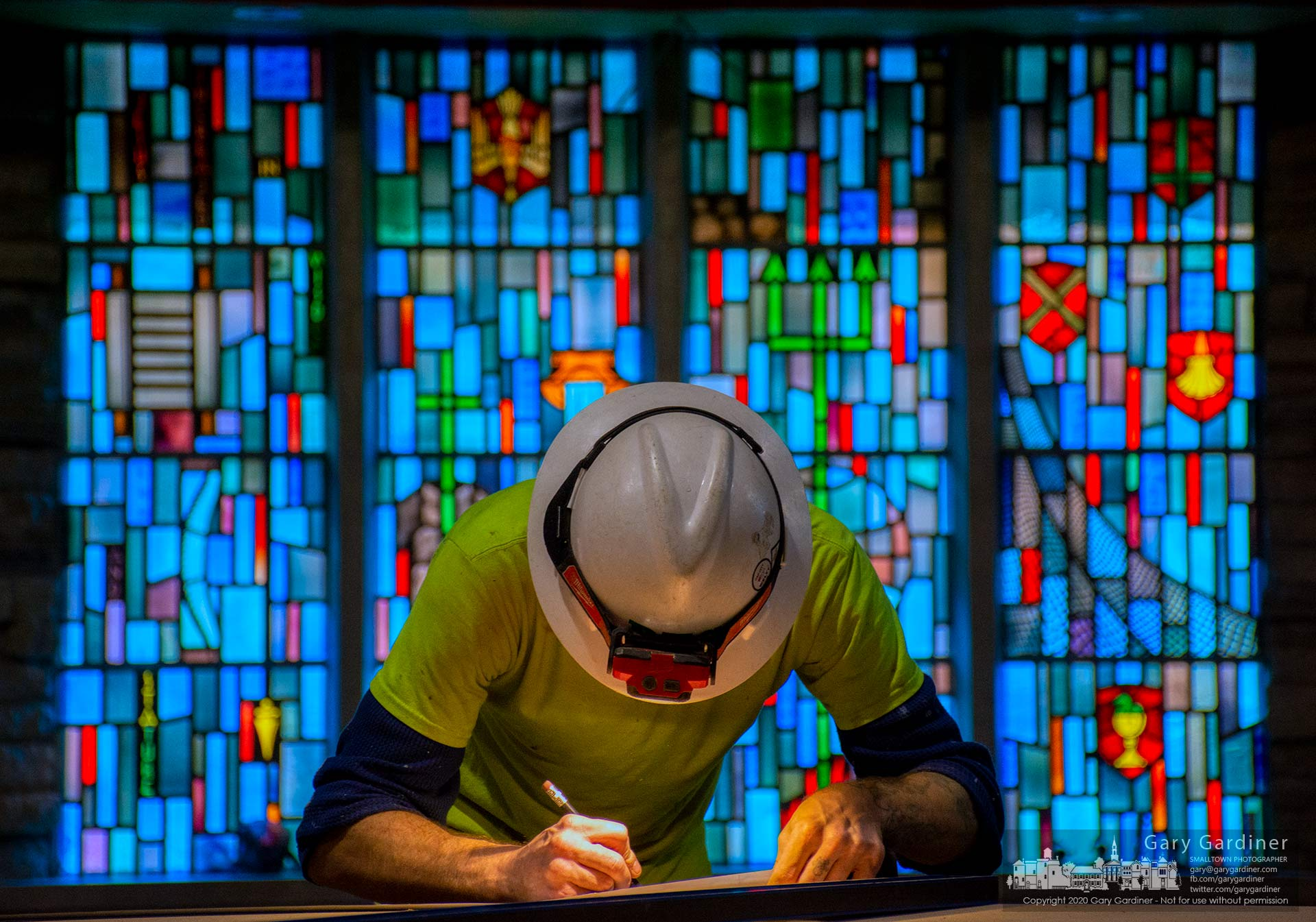 A carpenter measures a piece of fiberboard before cutting it for installation as an overhang over sections of stain glass inside the Church of the Messiah where contractors are working to complete work in time for Easter. My Final Photo for Feb. 18, 2020.