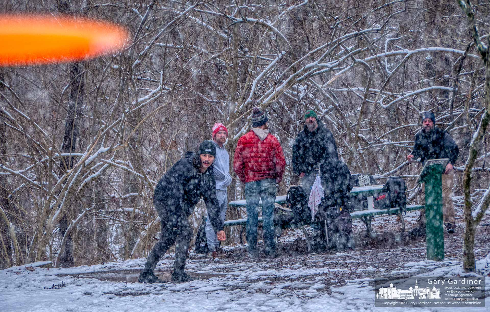 A group of disc golfers watch with surprise as one of their discs flies into the face of a photographer standing beside a tree on the course. My Final Photographer for Feb. 9, 2020.