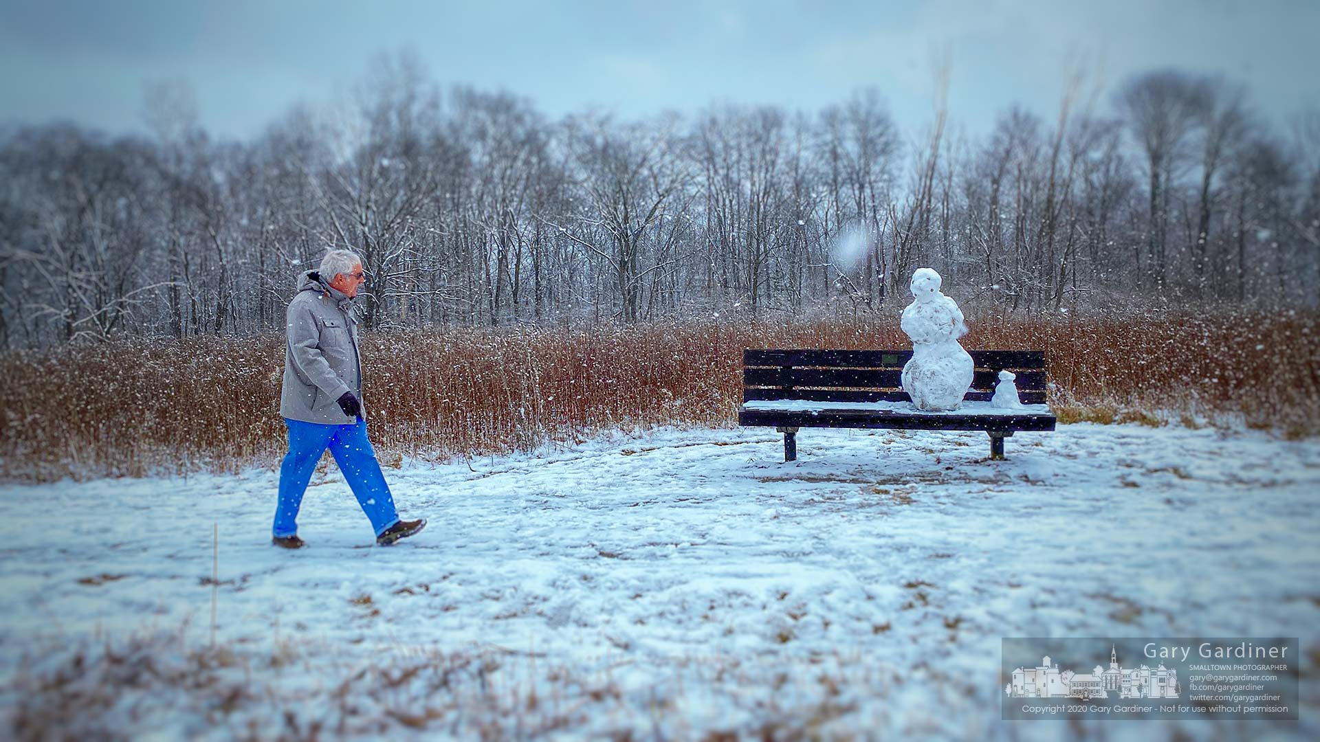 A man turns to look at a four-eyed snowman and his smaller companion built on a bench as he walks on a section of the Spring Creek Trail at Sharon Woods Metro Park during Saturday afternoon's snowfall. My Final Photo for Feb. 8, 2020.