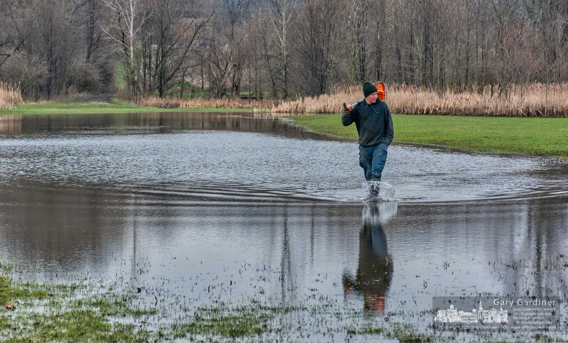 A contractor trods through a flooded field near the Westerville Community Center looking for relatively dry access to measure where the parks department plans a bridge to connect the center addition to a new section of bike path. My Final Photo for March 23, 2020.
