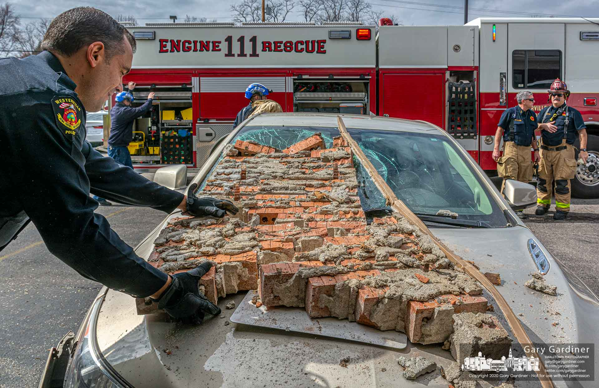 A Westerville police officer removes sections of brick that fell on a car when it crashed into a storefront at Hanby Square on South State Street. My Final Photo for March 12, 2020.