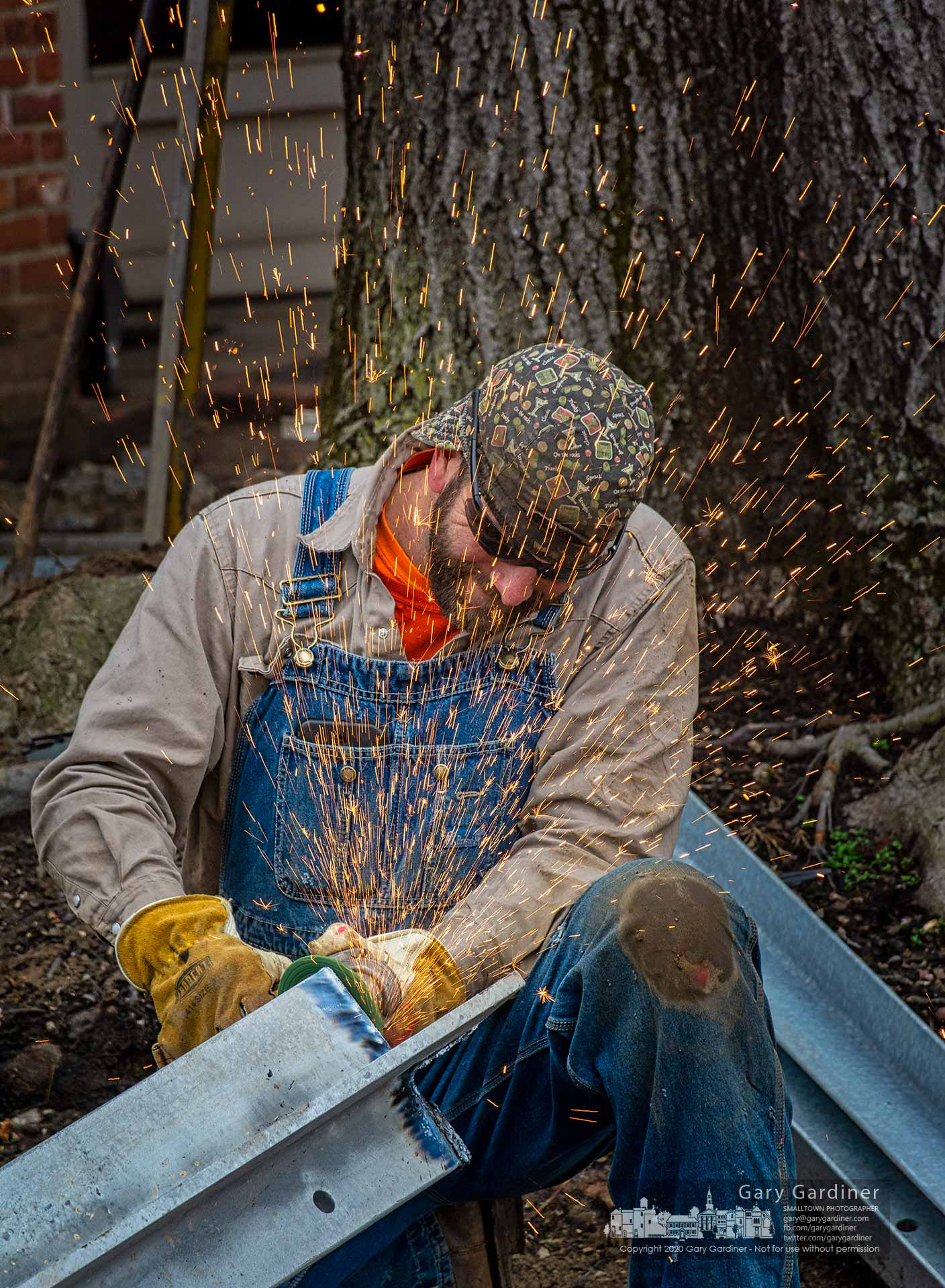 Sparks fly from a grinding wheel smoothing a steel beam surface before being welded into the supports for a platform around the oak tree in the brick walk at Java Central. My Final Photo for March 24, 2020.