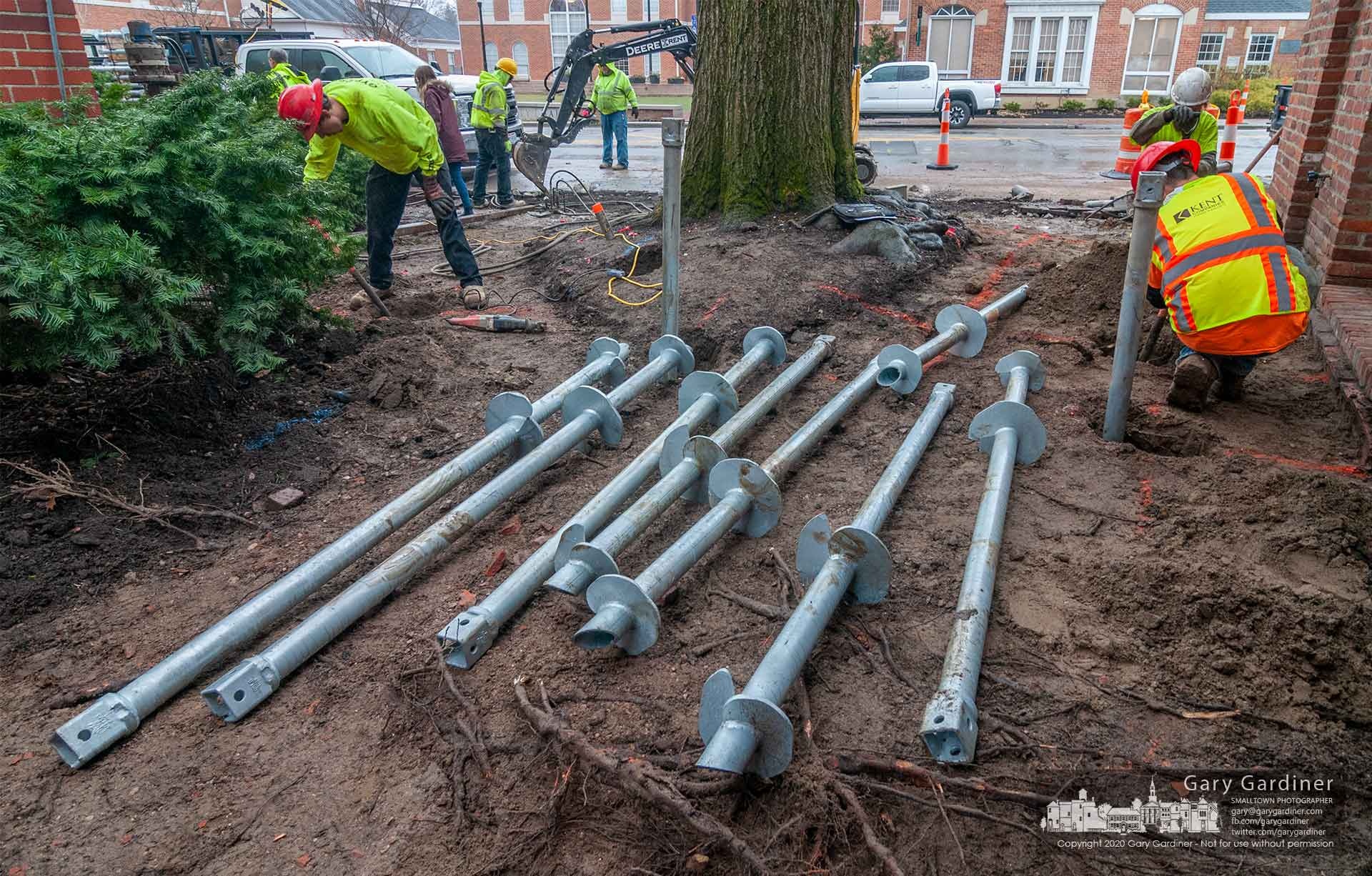 A work crew installs steel floating anchor posts around the heritage oak tree next to Java Central. The posts will eventually hold a short deck that will surround the tree. My Final Photo for March 11, 2020.