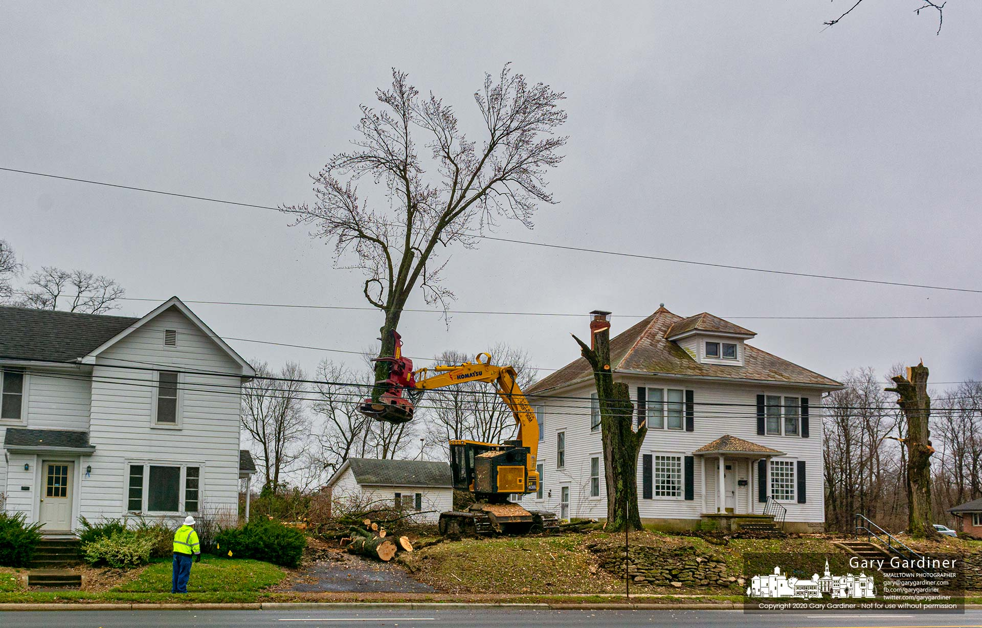 A section of a tree trunk is carried to the rear of the houses on South State Street where trees and the houses will be removed to make way for business buildings and apartments. My Final Photo for March 19, 2020.