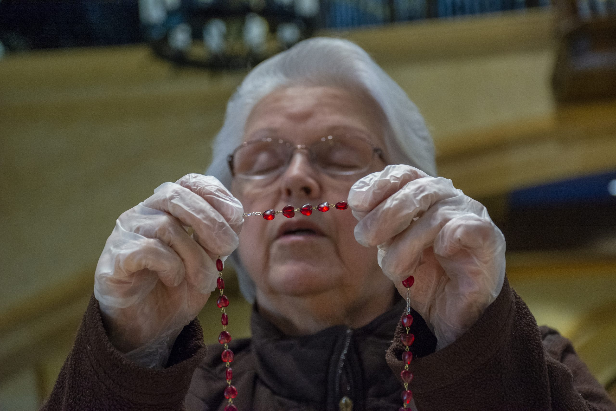 Sherry Gardiner wears protective gloves as she offers prayers at St. Paul the Apostle Catholic Church in Westerville, Ohio. Catholic churches in Ohio closed masses to the public in fear of spreading the coronavirus to parishioners. The church is open during the afternoon for parishioners. My Final Photo for March 17, 2020.