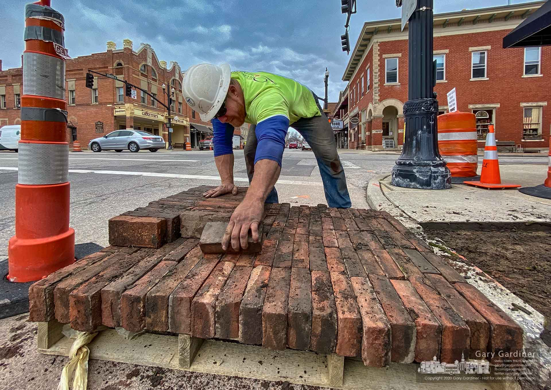 A brick mason removes sidewalk bricks from the corner of State and College where contractors are in the beginning stages of replacing the sidewalks and building new curbs as part of the Uptown Improvement project. My Final Photo for March 16, 2020.