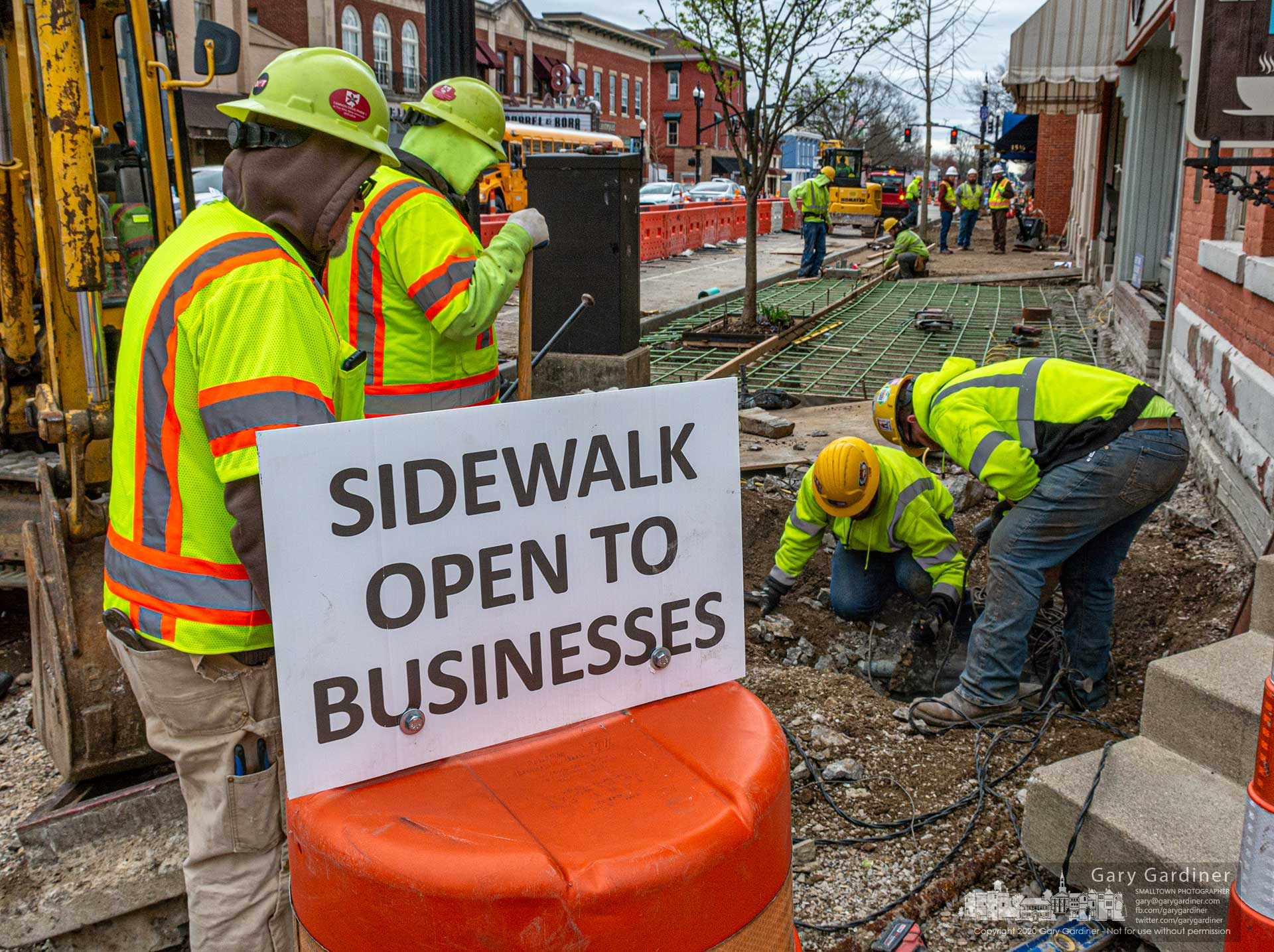 A sign noting businesses are open on the west side of State Street during sidewalk rebuilding appears inaccurate as workers lay reinforcing rods and forms for new sidewalks to be poured later in the week. My Final Photo for March 30, 2020.