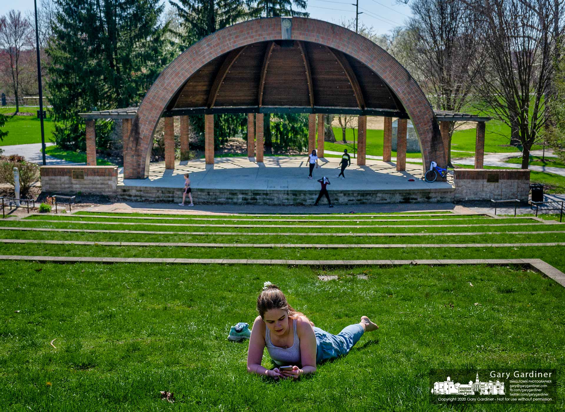 A young woman checks her phone during a break in her walk through Alum Creek Park on West Main Street where other visitors practice dance steps or athletes run the stairs. My Final Photo for April 6, 2020.
