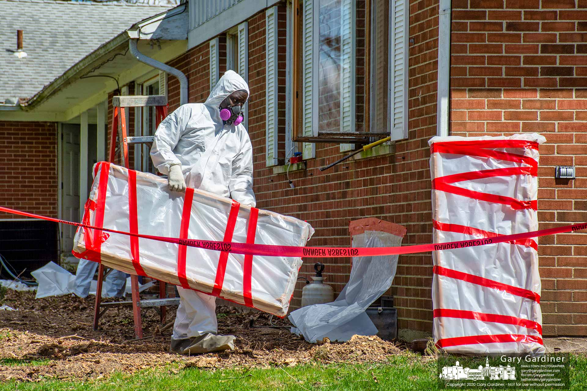 A contractor wearing safety gear removes an asbestos-laden window wrapped in plastic from the old McVay home on Hempstead where the Westerville parks department will demolish the building and party house to make way for a new park. My Final Photo for April 2, 2020.