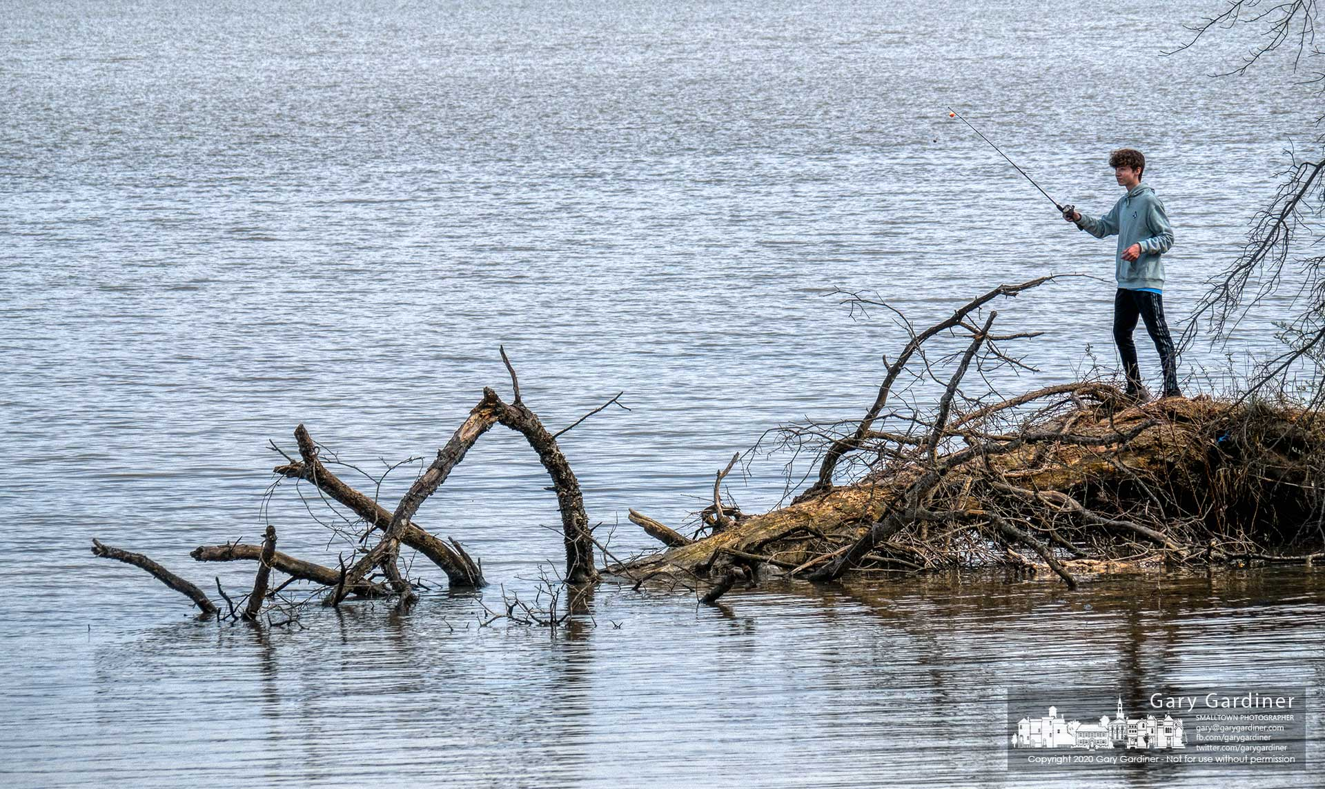 A young angler tries his luck casting along the length of a fallen tree at the edge of Hoover Reservoir. My Final Photo for April 19, 2020.