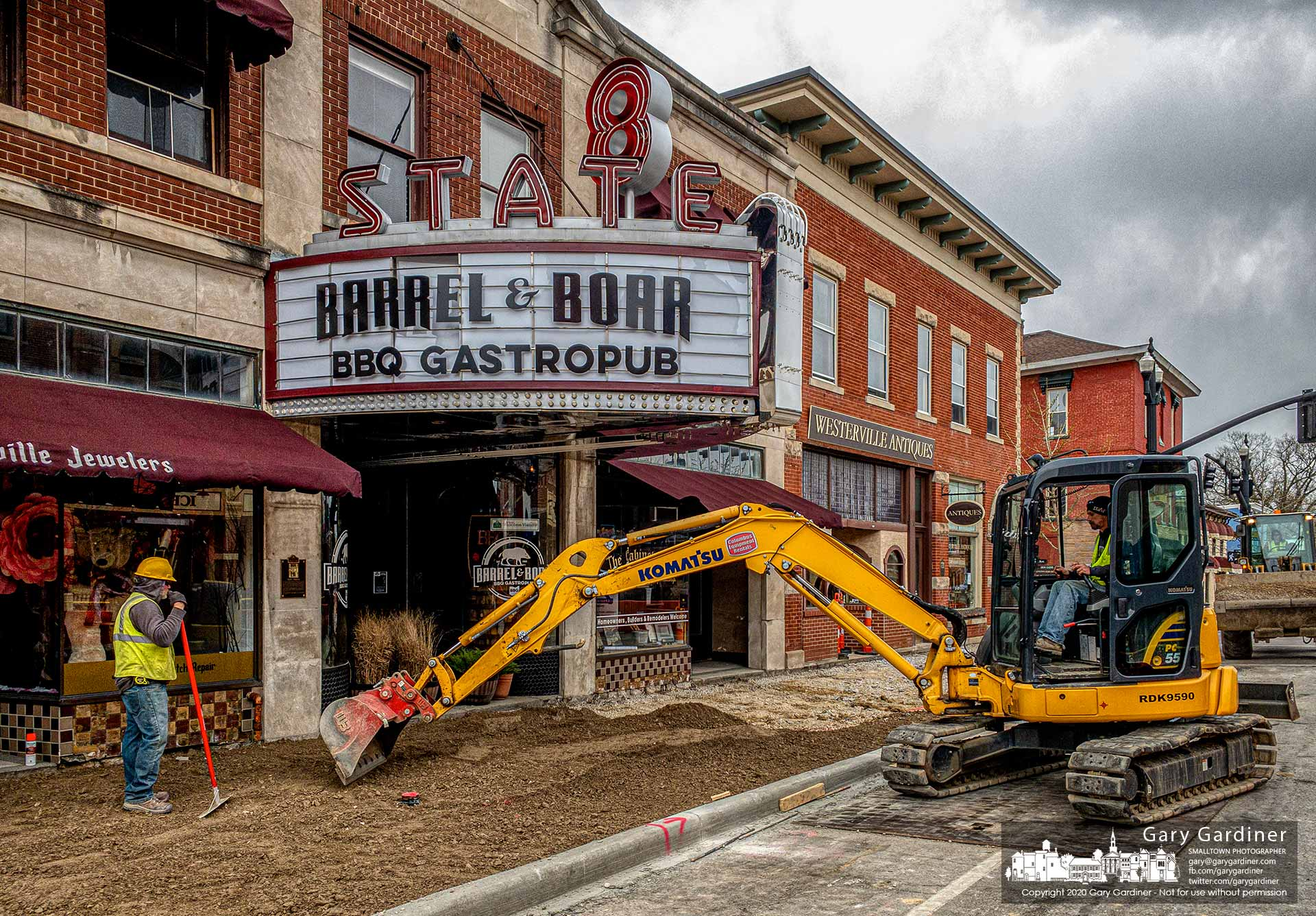 A construction worker spreads and levels dirt for a new sidewalk beneath the 8 State marquee as work on the Uptown Improvement Project accelerates with store closing and traffic less than normal because of coronavirus restrictions. My Final Photo for April 15, 2020.