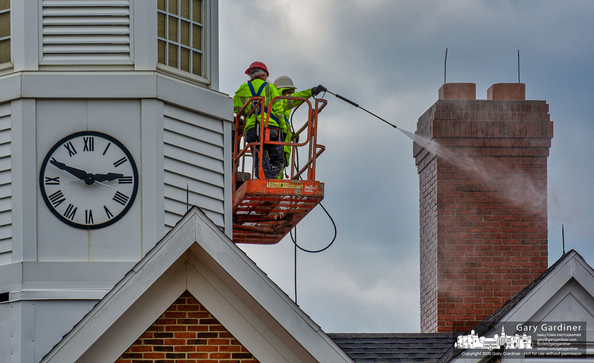 A cleaning crew power washes the chimney on city hall where parts of the building are undergoing maintenance. My Final Photo for May 12, 2020.