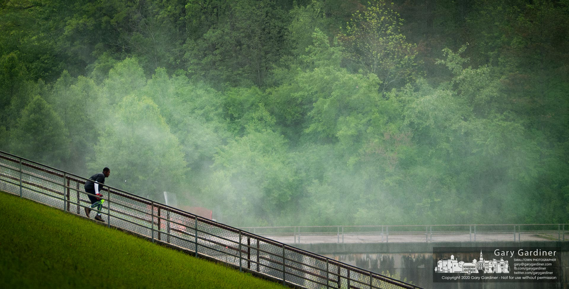 An athlete makes his way Wednesday morning down the stairs at Hoover Reservoir past a mist formed by the discharge from the dam where the water approached nearly two feet to the 900-foot depth measure on the dam. My Final Photo for May 20, 2020.